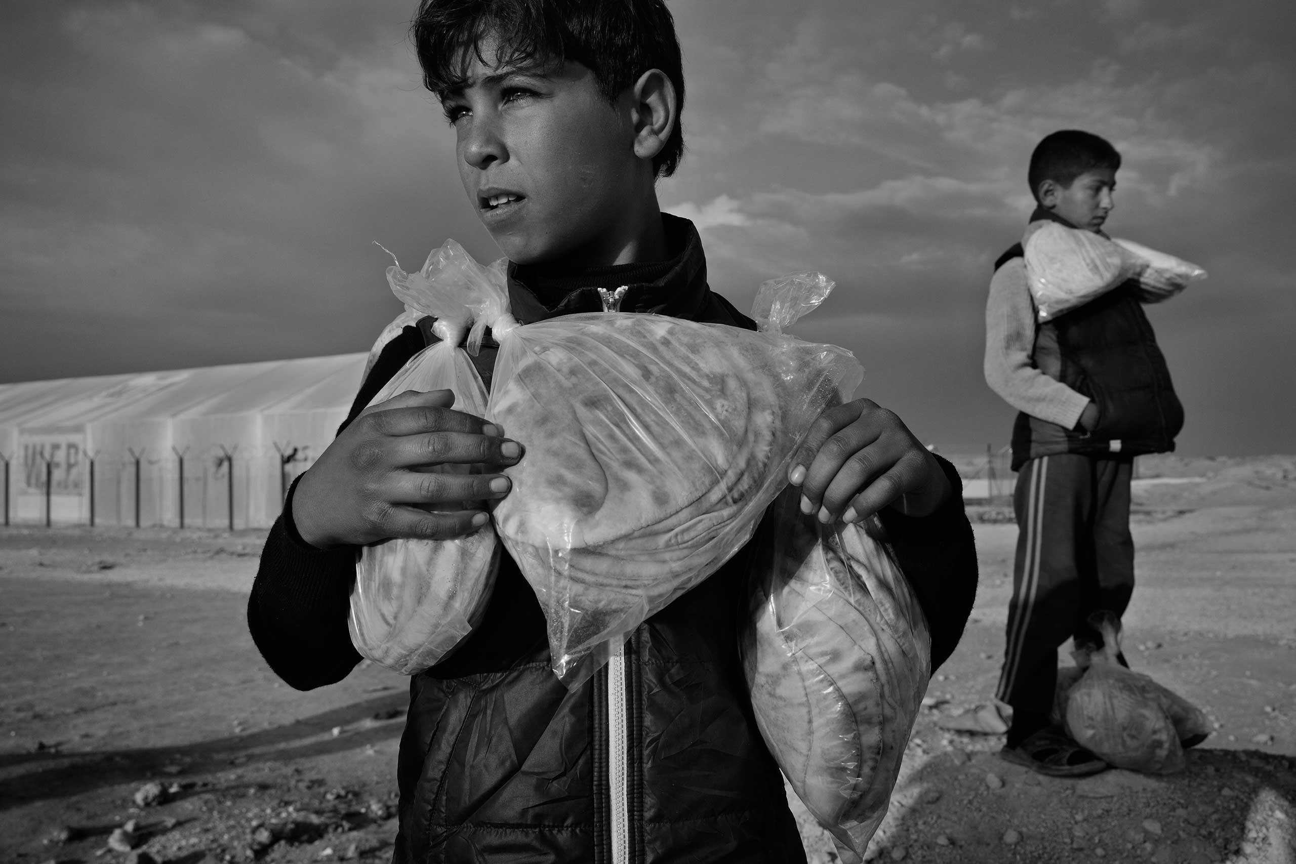 December 2013. Za'atari refugee camp, Jordan. Syrian boys carry their daily bread ration supplied by the World Food Programme.  From  Syrian Refugees by James Nachtwey