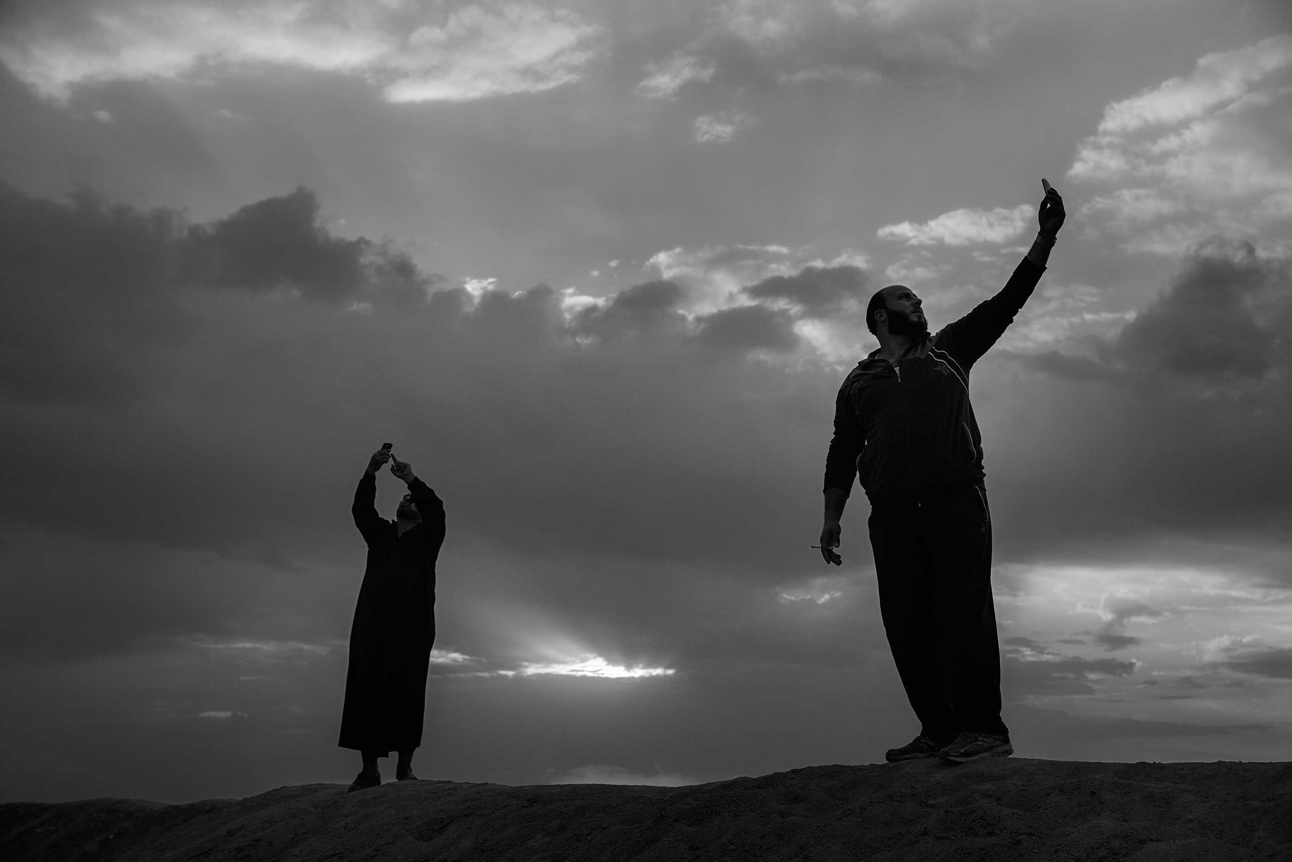 December 2013. Za'atari refugee camp, Jordan. Residents of the camp search for a clear cell-phone signal to call Syria.  From  Syrian Refugees by James Nachtwey