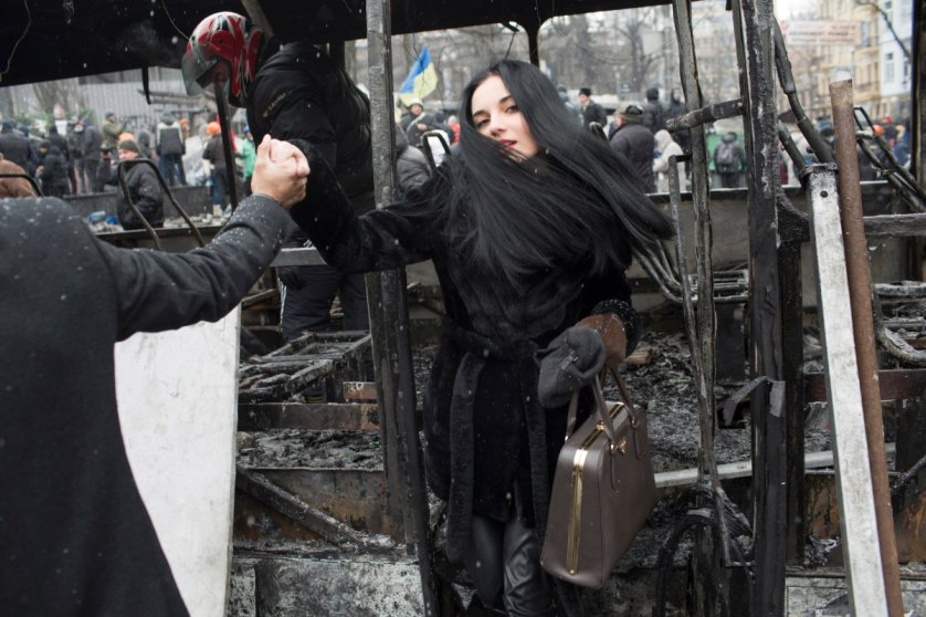 A young woman steps off a destroyed vehicle that was used to form a barricade during a lull in violent clashes between demonstrators and police forces on Hrushevsky Street in central Kyiv. January 21, 2014