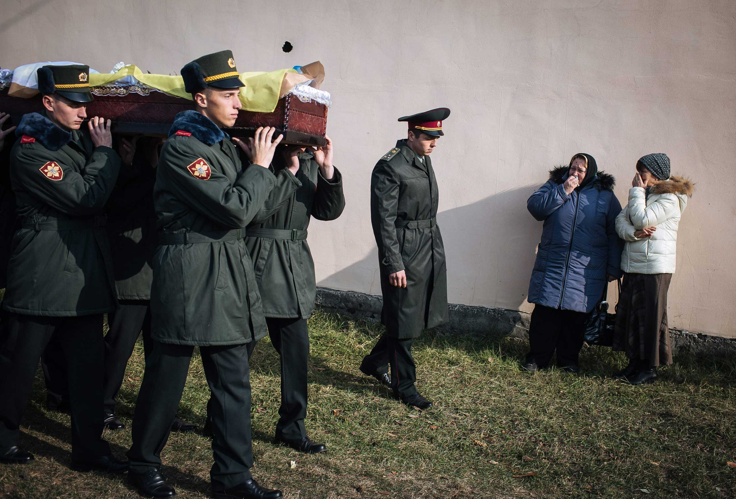 Oct. 31, 2014. Women react as soldiers carry a coffin with Fedor Lipchak, a Ukrainian serviceman of the Aidar Battalion who was killed in eastern Ukraine, during a funeral ceremony in Gurovschina village near Kiev, Ukraine.