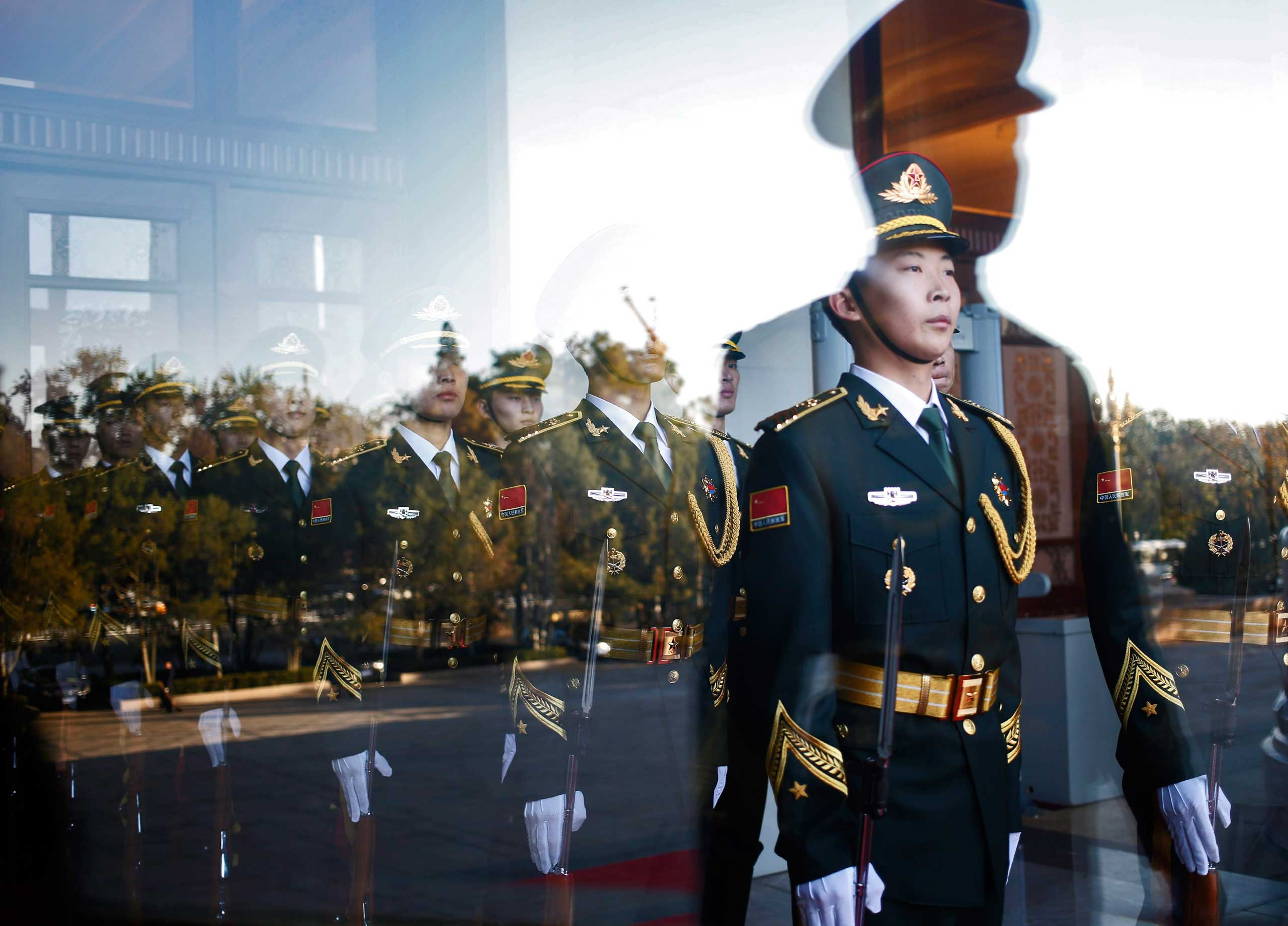 Nov. 3, 2014. Chinese honor guards are seen through a glass door before a welcome ceremony for the Emir of Qatar, Sheikh Tamim bin Hamad Al Thani, at the Great Hall of the People in Beijing. Qatar's Emir is in China for a state visit from Nov. 2 to Nov. 4.