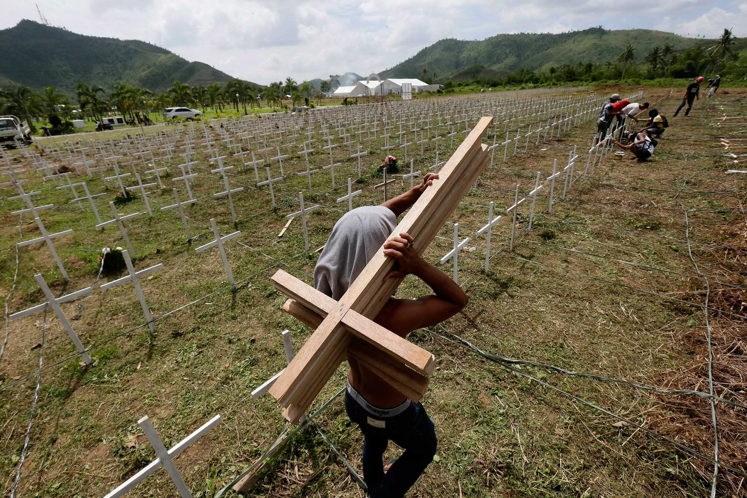 Nov. 5, 2014. Wooden crosses are pitched by workers at a new mass grave of about 3,000 typhoon Haiyan victims in Tacloban City, Philippines. One year after Haiyan left nearly 8,000 people dead or missing in the eastern Philippines, many survivors are still suffering from emotional distress despite being busy with physically rebuilding their lives.