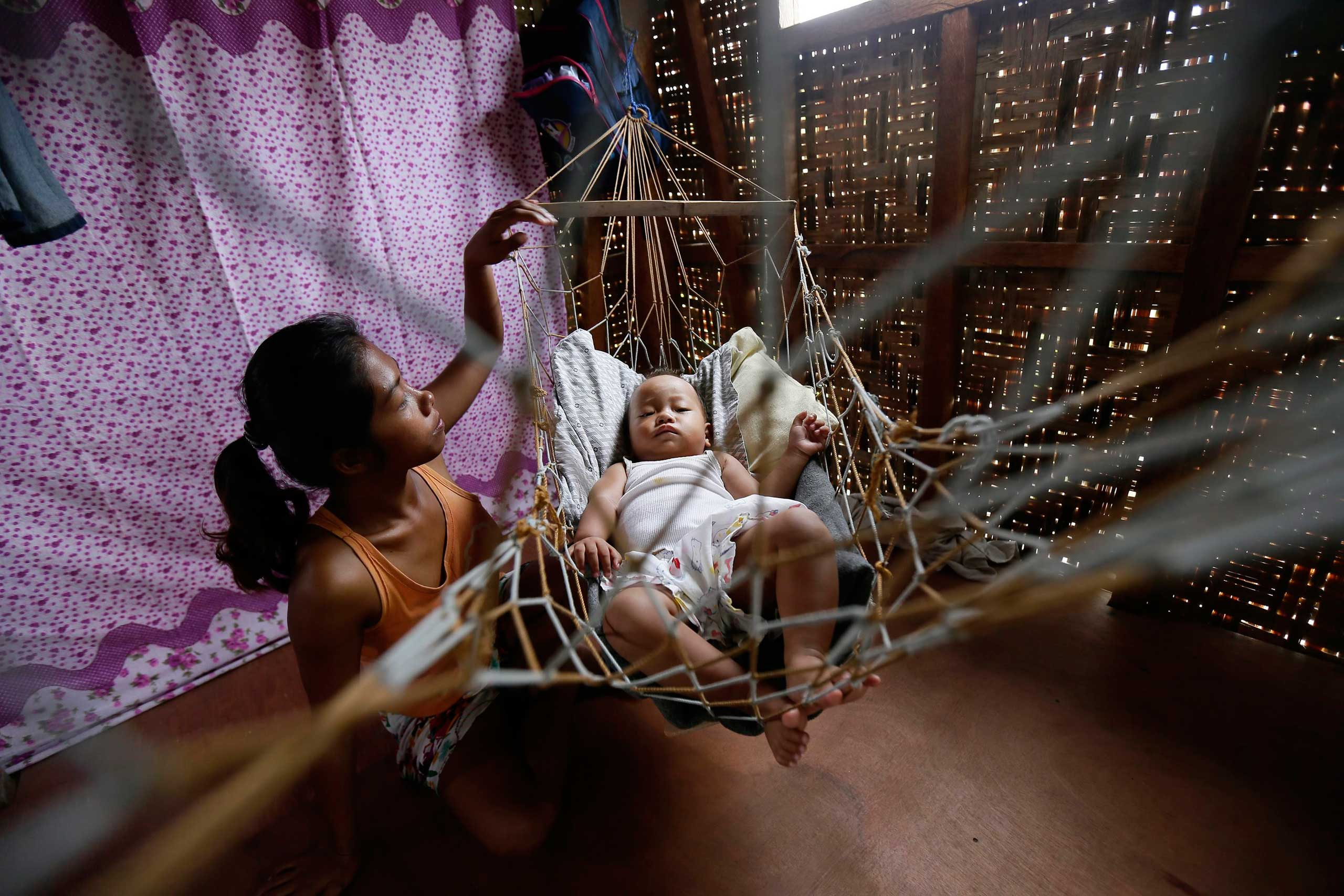 Nov 5, 2014. Emelie Sagales, 23, sits inside a hut next to her 1-year-old baby Bea Joy, who was born on Nov. 11, 2013, inside a dilapidated building which was damaged by the 2013 Typhoon Haiyan in Leyte Province, Philippines.