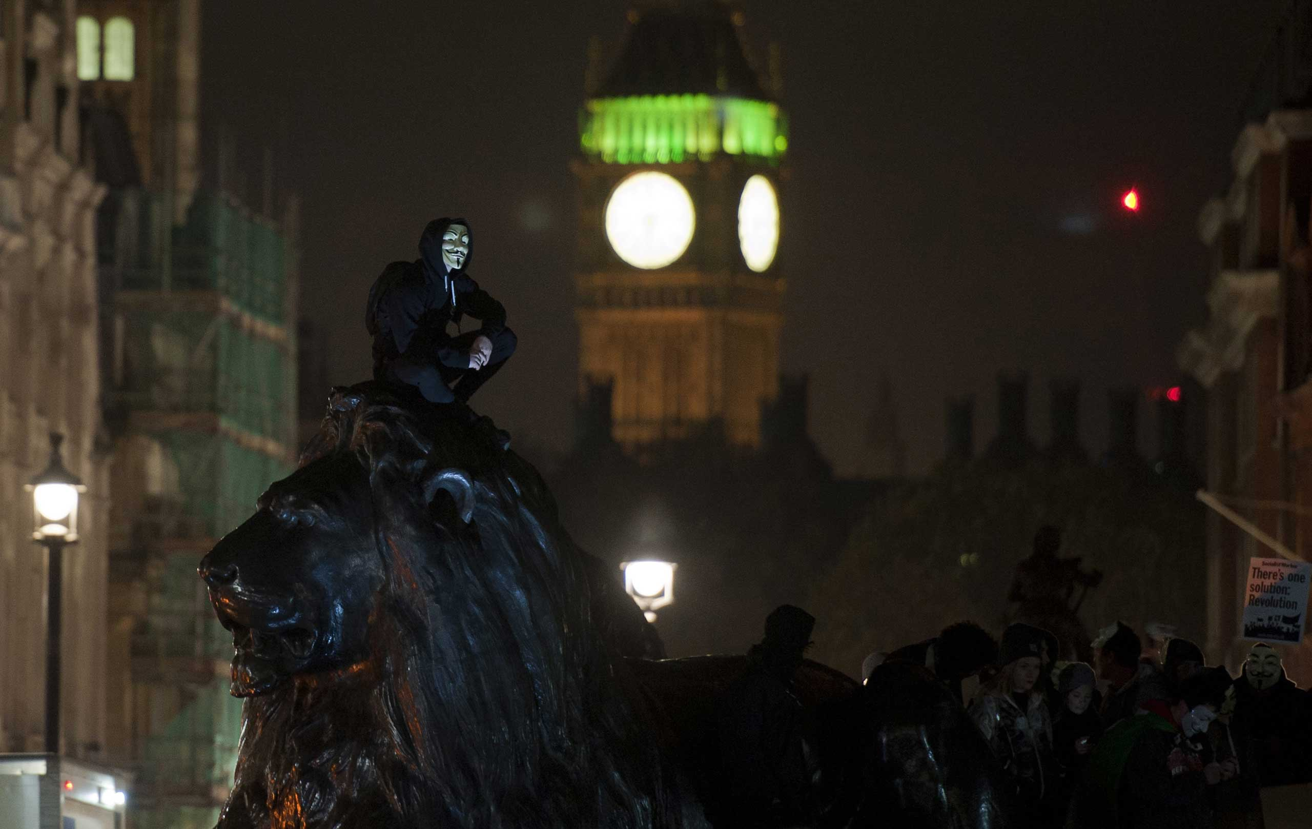 Nov. 5, 2014. A protester stands on a statue on Trafalgar Square during the Million Mask demonstration in London. The demonstration took place on Bonfire Night, the anniversary of the capture of Guy Fawkes, during his attempt to blow up the Houses of Parliament in 1605.