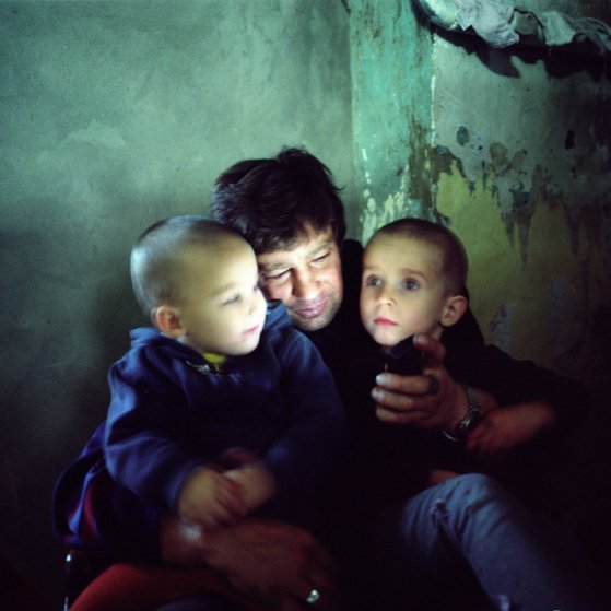 Sasha, who is HIV-positive, watches a video on his mobile phone with his child and grandson. Odesa, Ukraine, 2008