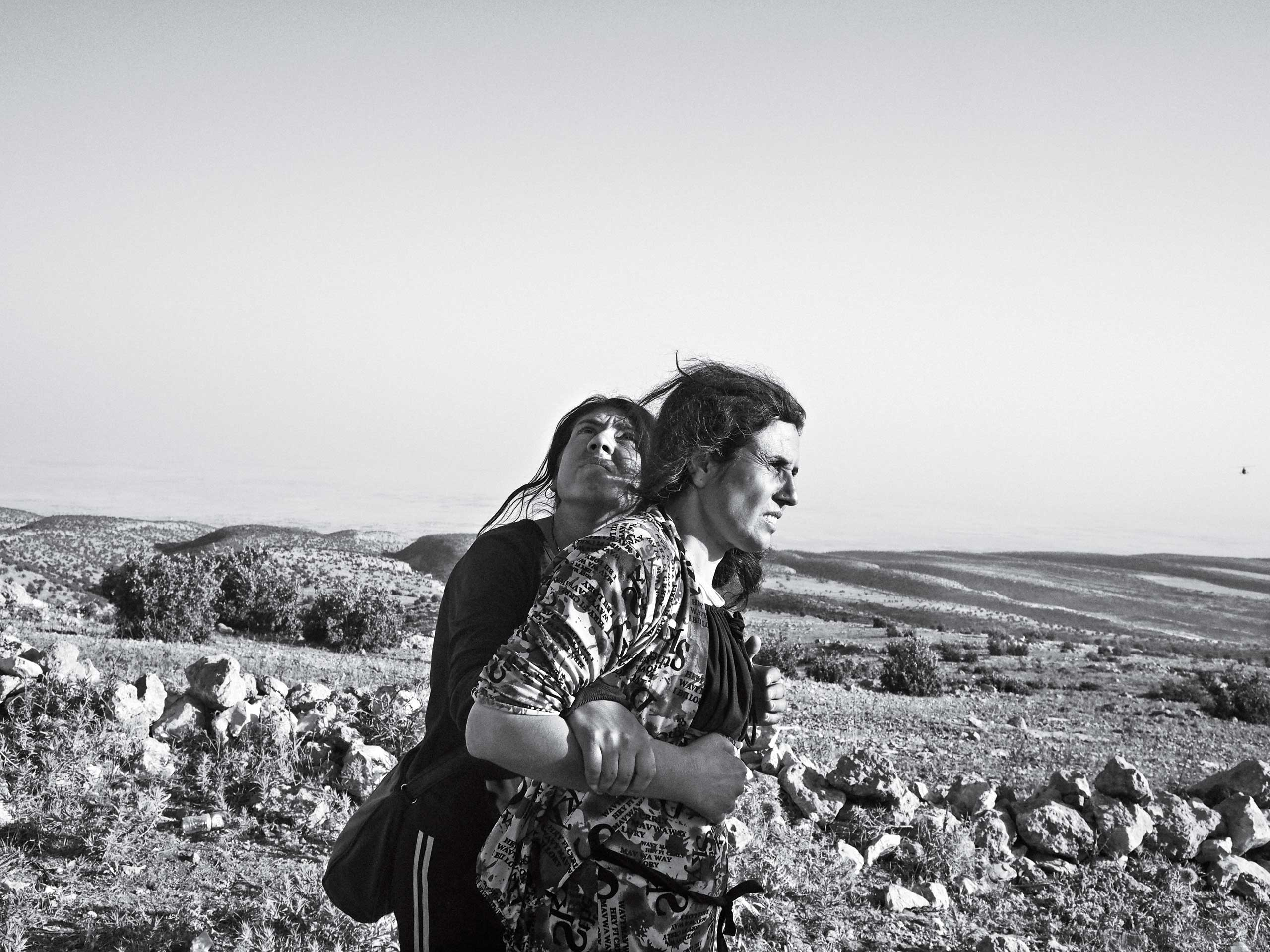 Sinjar Mountains, Iraq. August 12, 2014. Yezidi women stranded in the Sinjar Mountains wait for the arrival of a rescue helicopter.From  Tragedy on Mount Sinjar