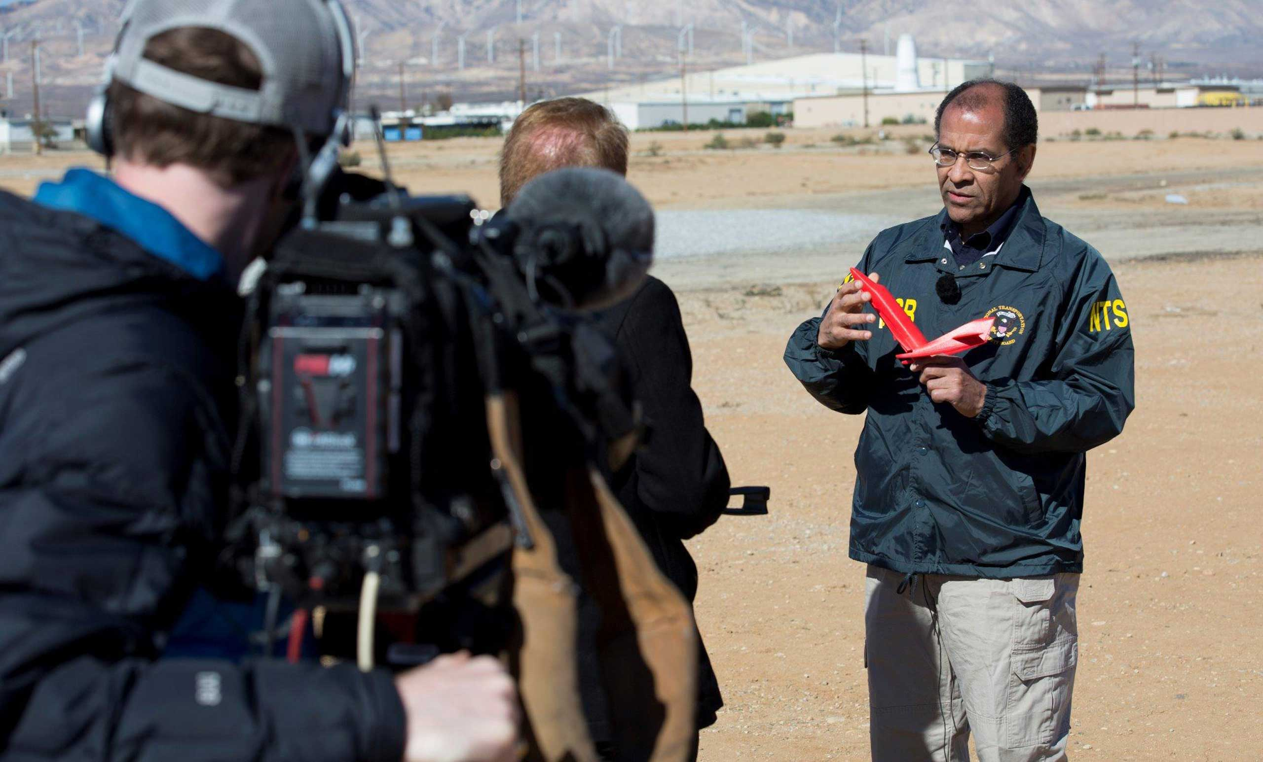Acting NTSB Chairman Christopher Hart uses a model to demonstrate how the SpaceShipTwo rocket plane was supposed to  feather  its wings during an interview with the a video crew, Nov. 3, 2014.