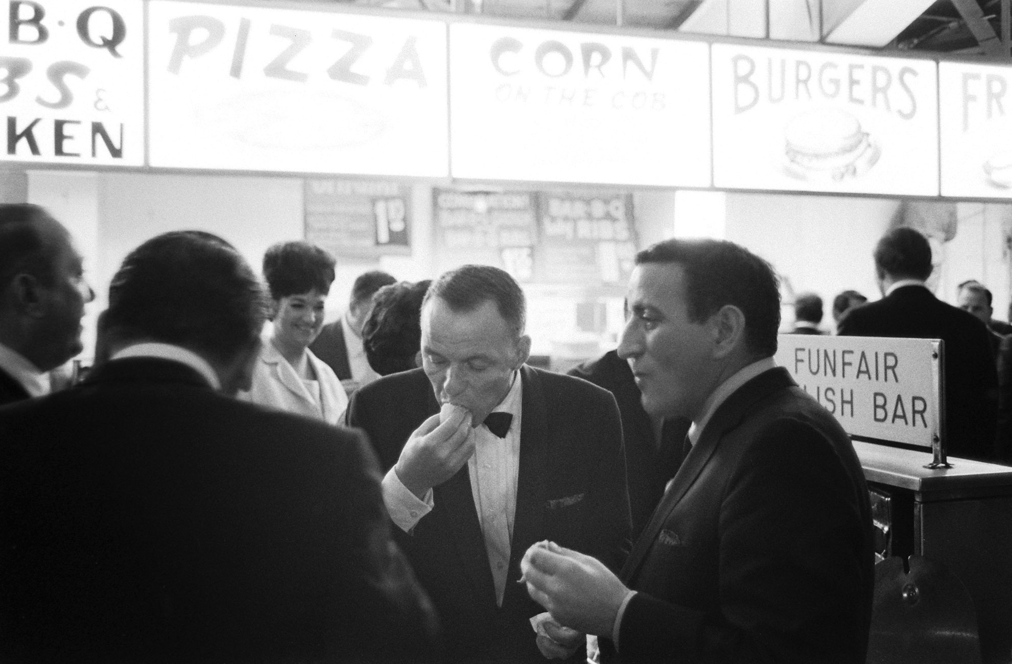 Tony Bennett, Frank Sinatra and friends eat some late-night hot dogs, Miami, 1965.
