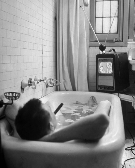 Writer Russell Finch enjoys a smoke, a bath and a TV show in 1948