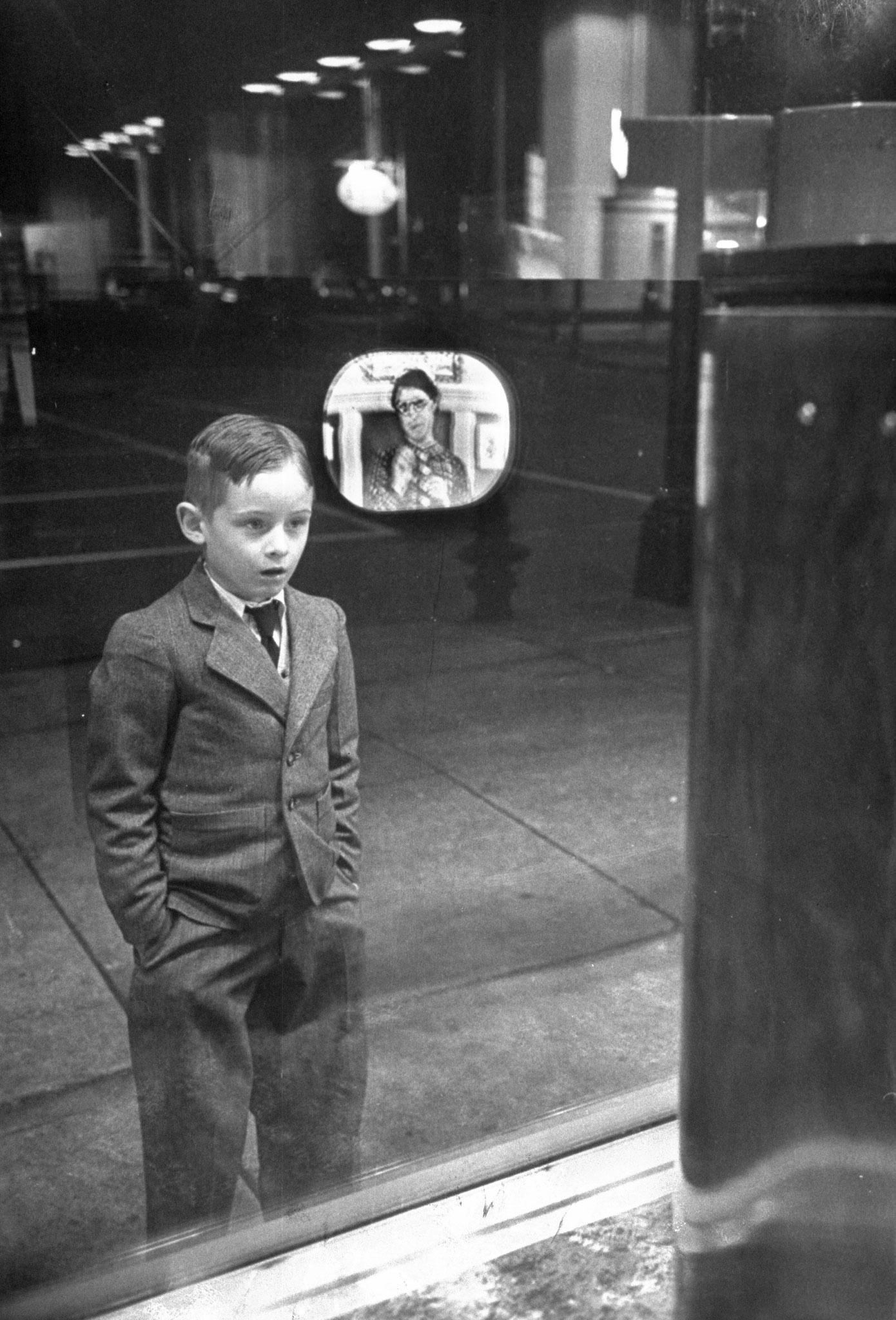 A boy watches TV in an appliance store window in 1948.