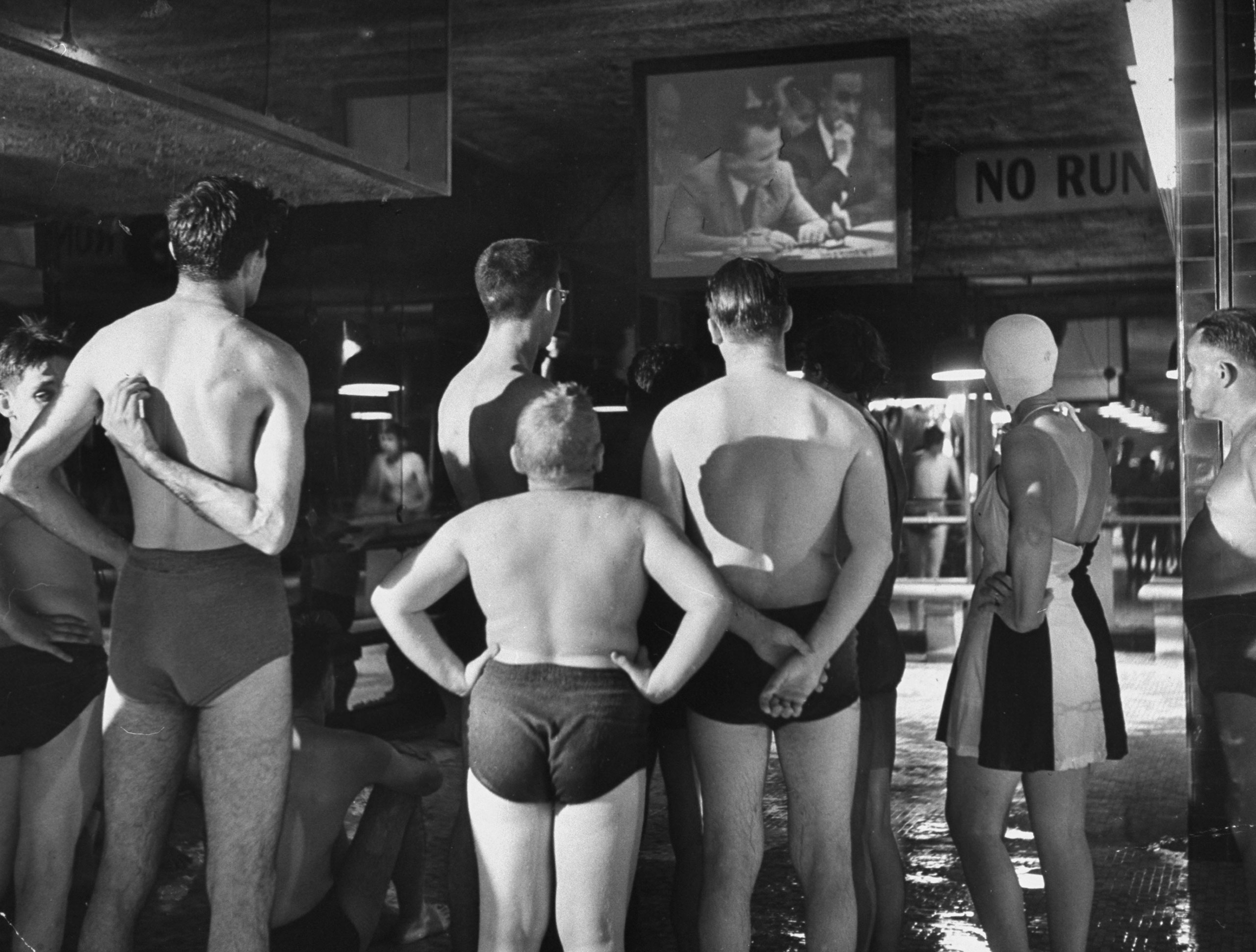 A group of swimmers at an indoor pool watch the Russian ambassador to the United Nations, Jacob Malik, filibustering in the UN Security Council in 1950.