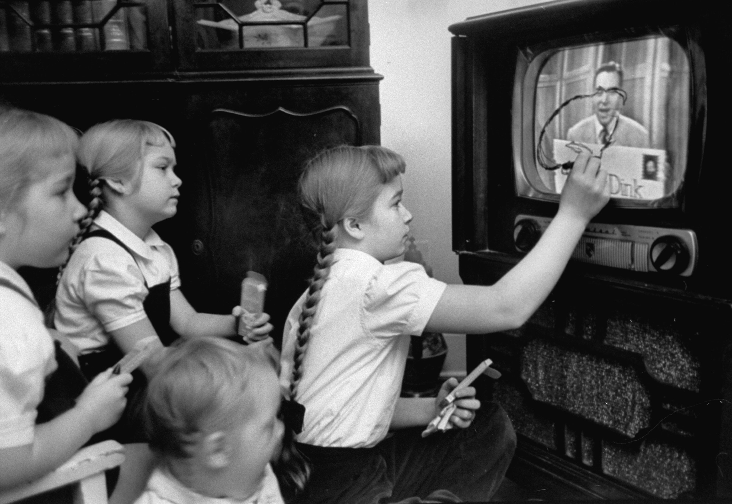 "Six-year-old girls use a ""Winky Dink"" drawing kit on their home TV screen as they watch the kids' program, 1953. The show, which aired for four years in the 1950s, has been cited as ""the first interactive TV show,"" especially in light of its ""magic drawing screen"" — a piece of plastic that stuck to the TV screen, and on which kids (and, no doubt, some adults) would trace the action on the screen."