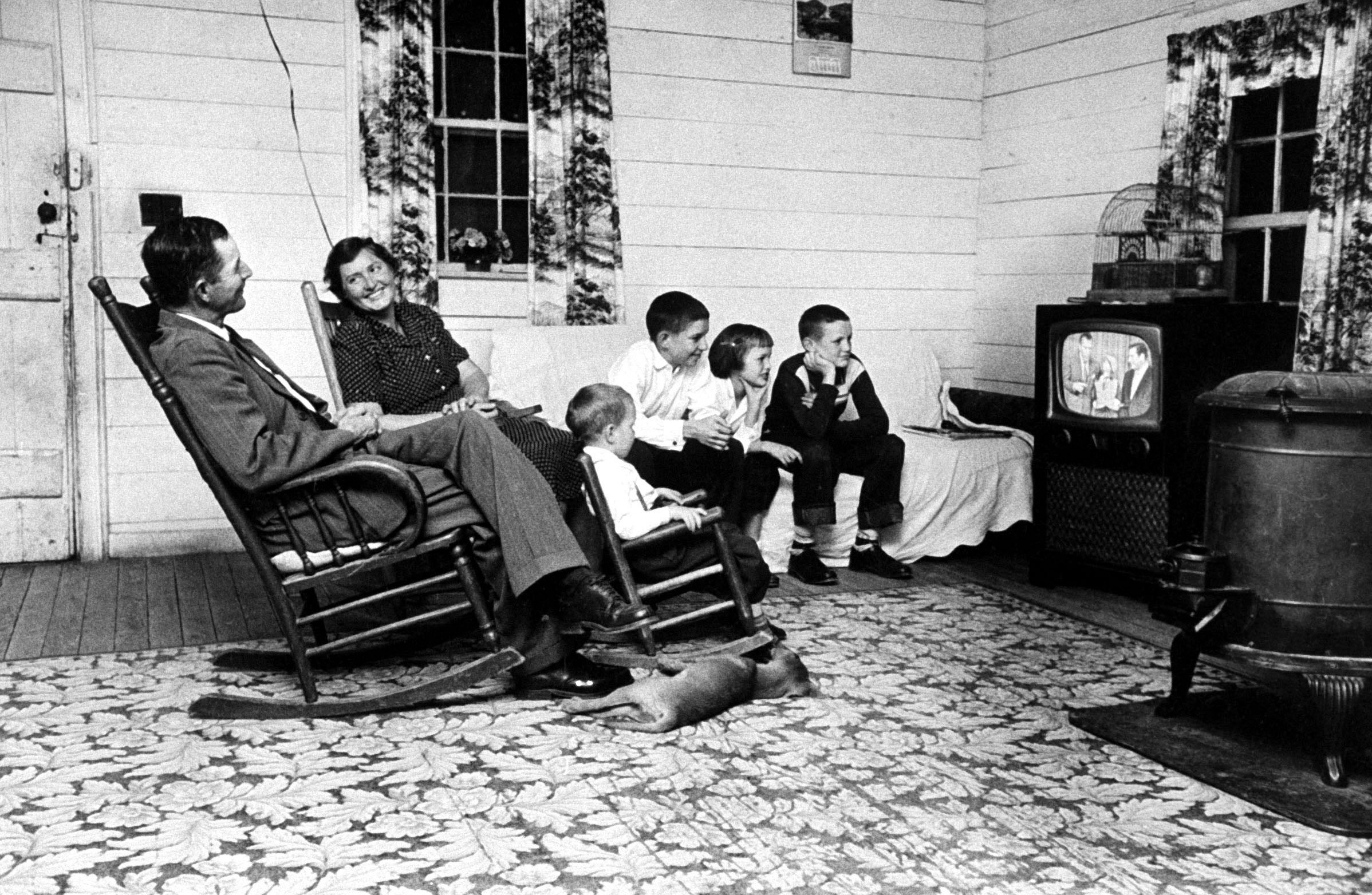 Tenant farmer Thomas B. Knox and his family watch Ed Sullivan and ventriloquist Rickie Layne on <i>The Ed Sullivan Show</i> in 1958.