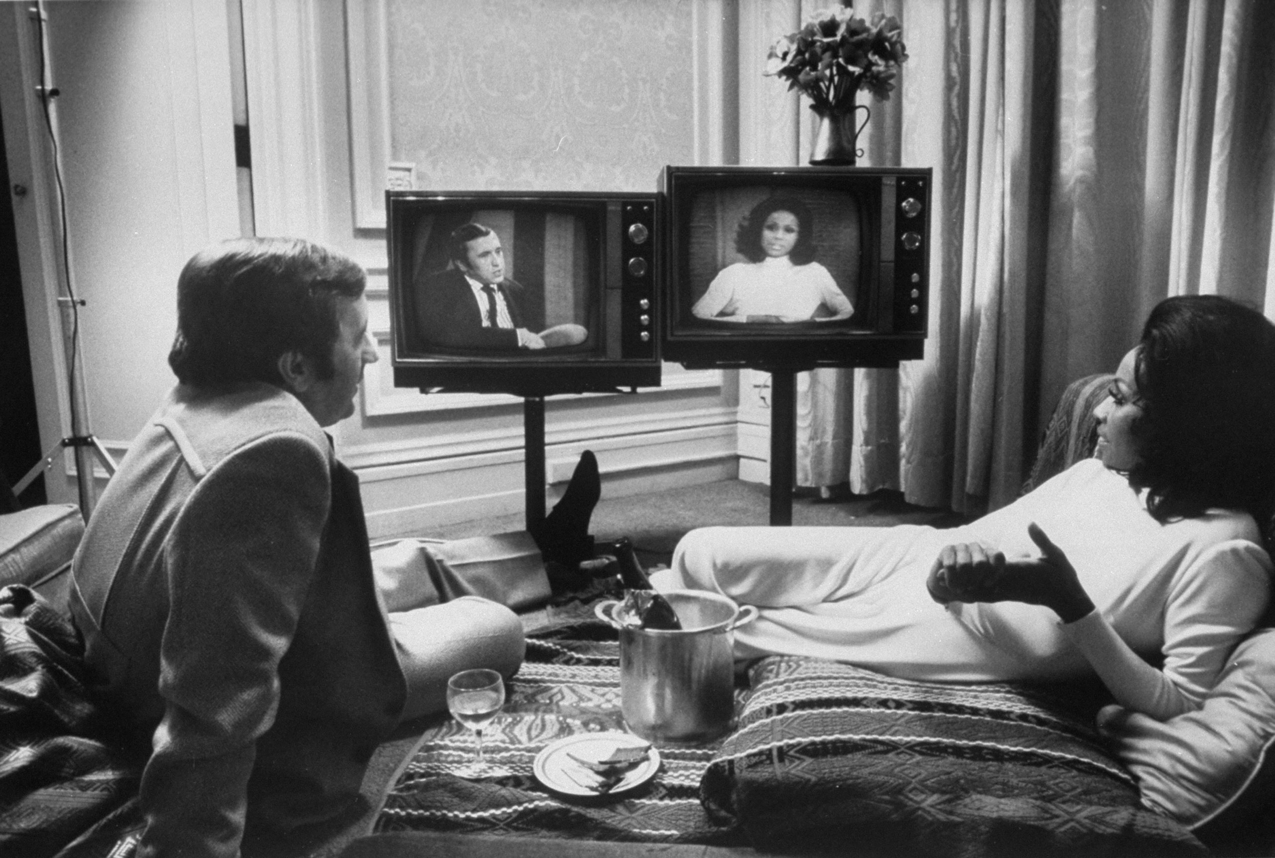Actress Diahann Carroll and journalist David Frost watch themselves on separate talk shows. Carroll and Frost were engaged for a while, but never married.