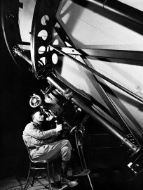 Astronomer Edwin Hubble looks though the eyepiece of the 100-inch telescope at California's Mt. Wilson Observatory, 1937.