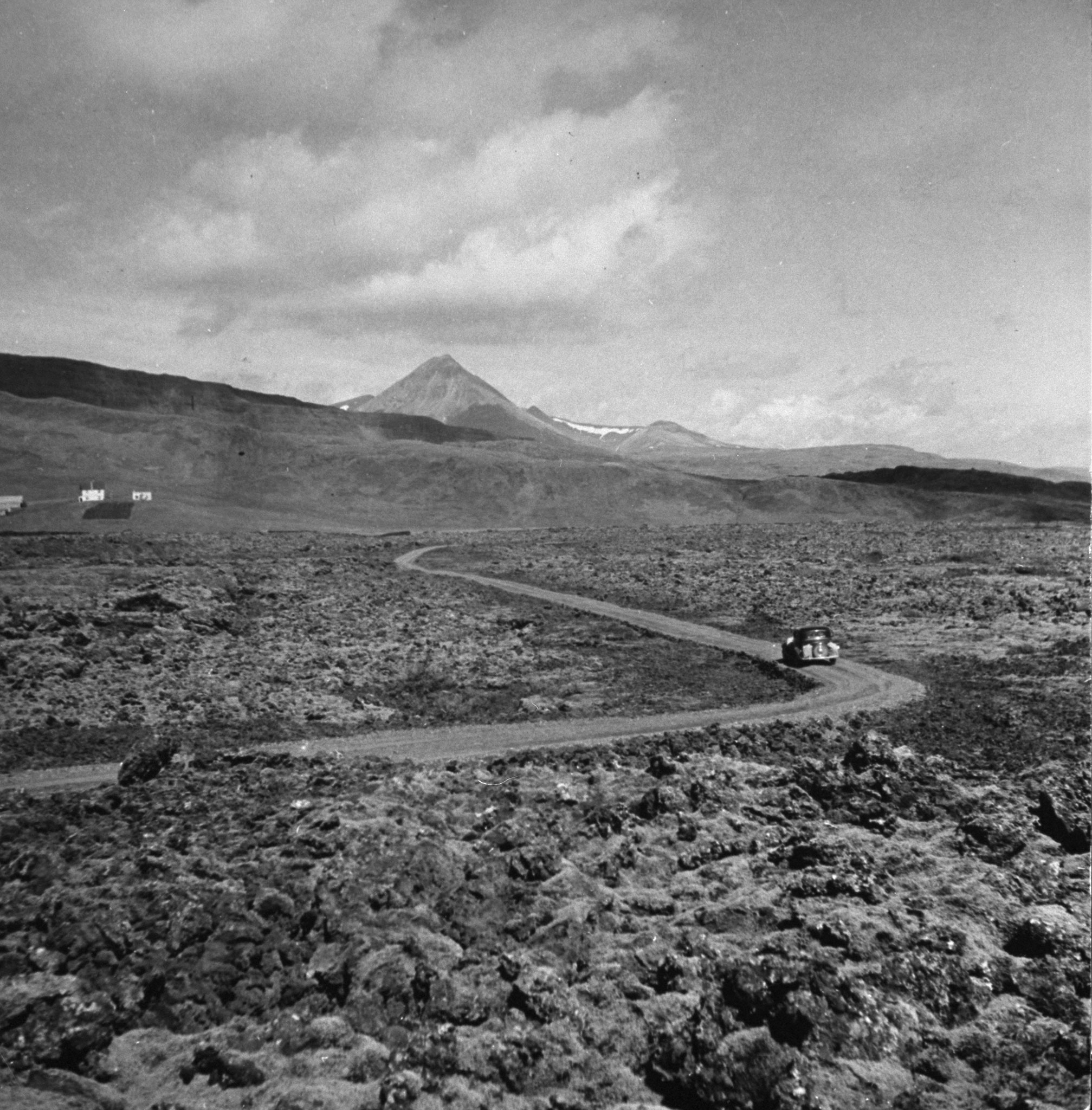 """<b>Caption from print:</b> """"Land without railroads. The roads in Iceland may seem inadequate to the American tourist, but in view of the rough climate and the sparse and scattered population the more than 1,330 miles of roads are an excellent achievement. For hours you sometimes drive on roads like this through miles and miles of lava fields which would be impassable for man or horse."""""""