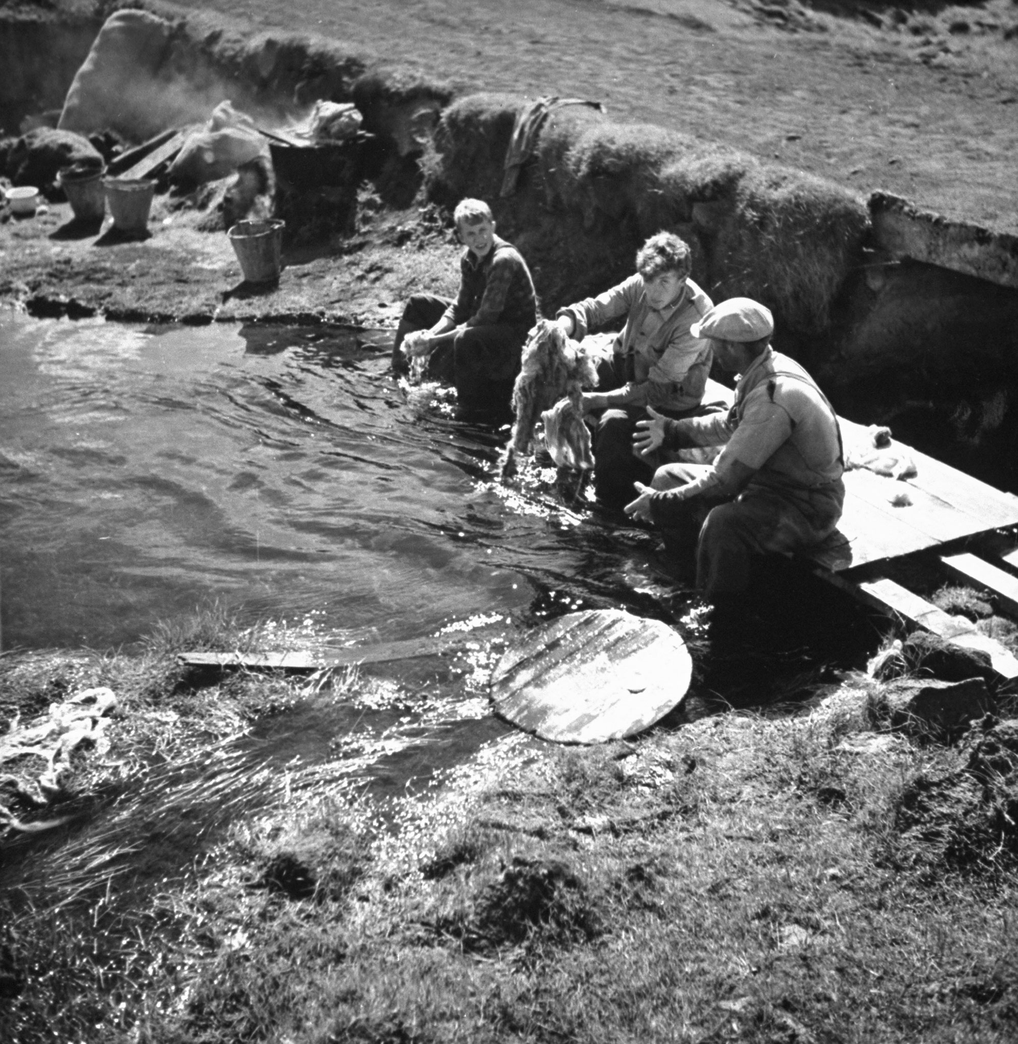 """<b>Caption from print:</b> """"Photo shows the primitive way in which wool is washed. While the women boil the wool in a large pot on an open fire, the men are occupied with rinsing it in the clear water of the brook."""""""