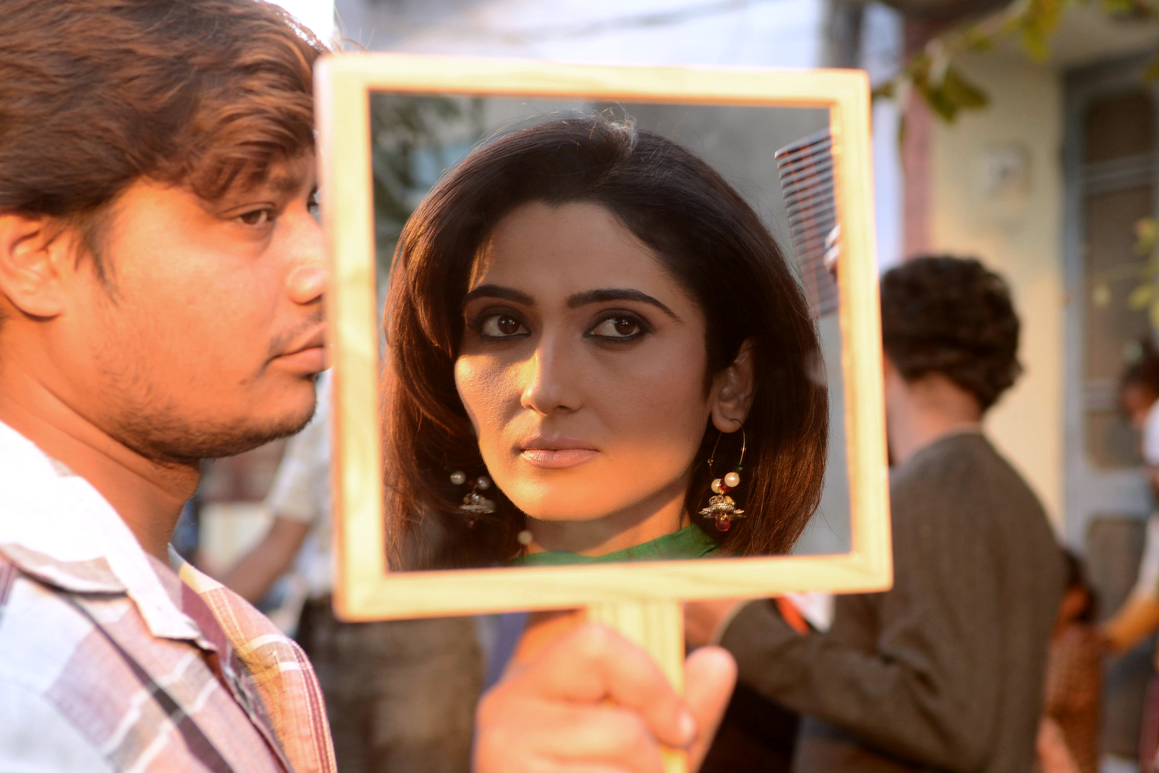 Actress Gauri Singh is reflected in a mirror as she adjusts her makeup during filming on the set of the Punjabi film 'Bolo Tara Rara' in Amritsar on November 16, 2012.