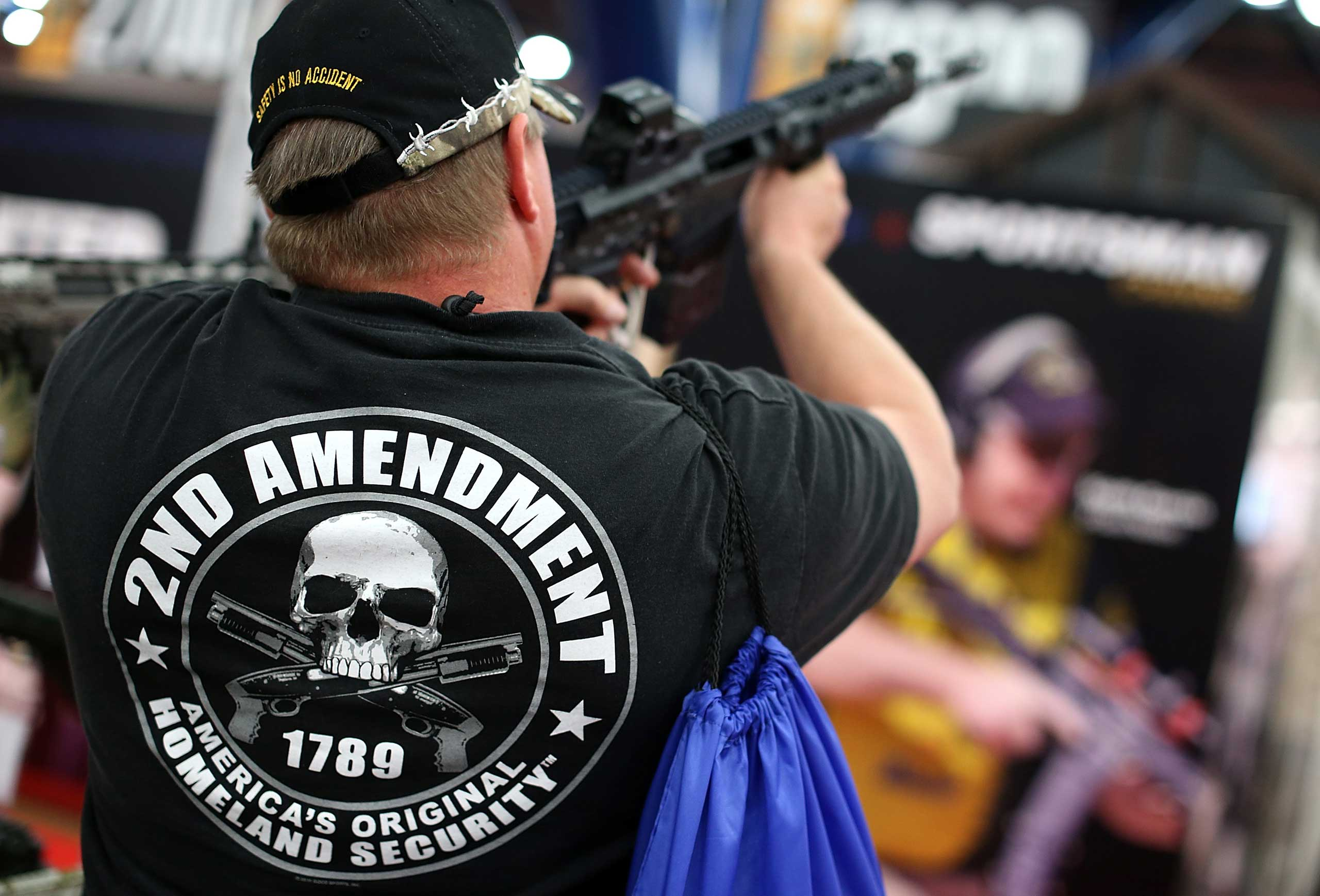 An attendee wears a 2nd amendment shirt while inspecting an assault rifle during the 2013 NRA Annual Meeting and Exhibits at the George R. Brown Convention Center on May 5, 2013 in Houston, Texas.