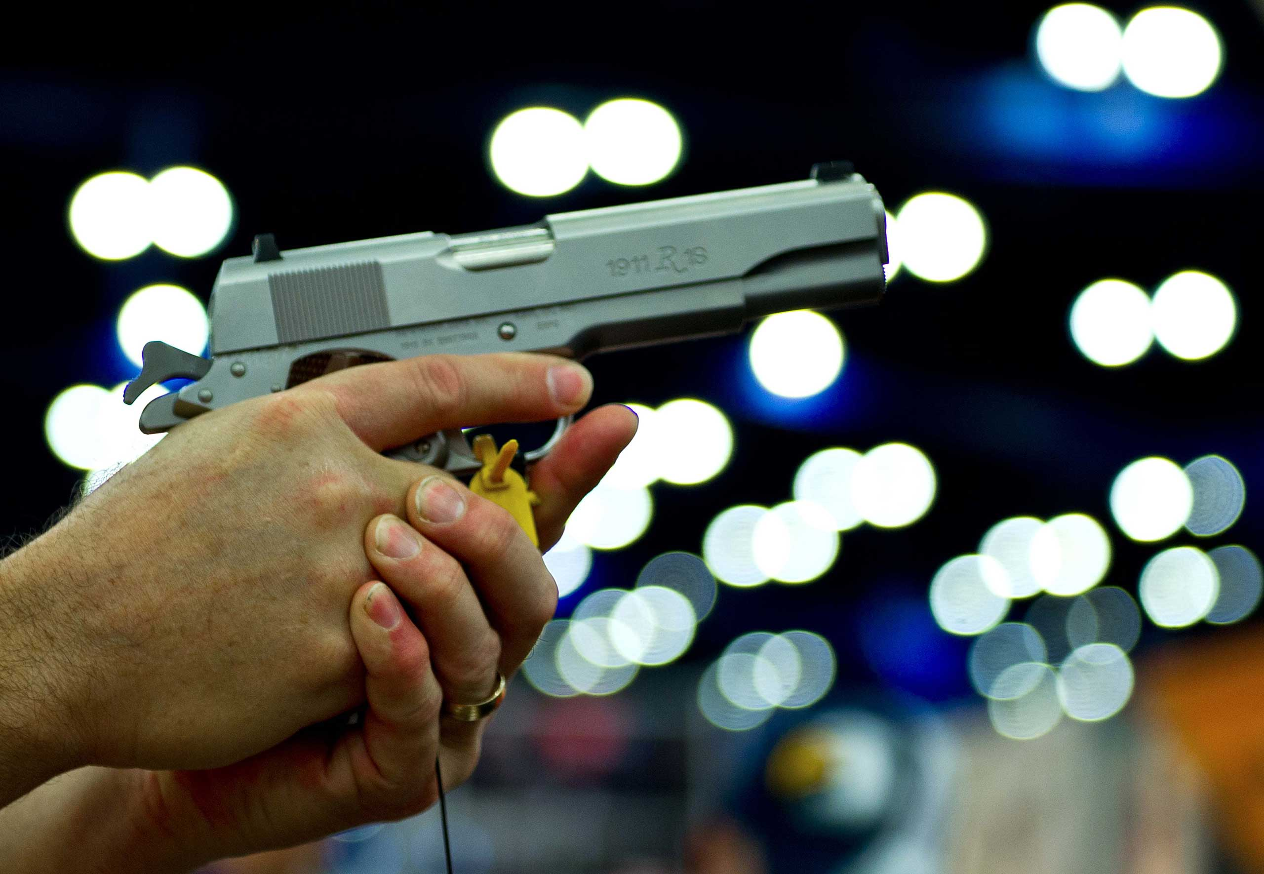 A convention goer handles a Ruger 1911 model semi-automatic pistol during the142nd annual National Rifle Association convention at the George R. Brown Convention Center on May 4, 2013 in Houston.