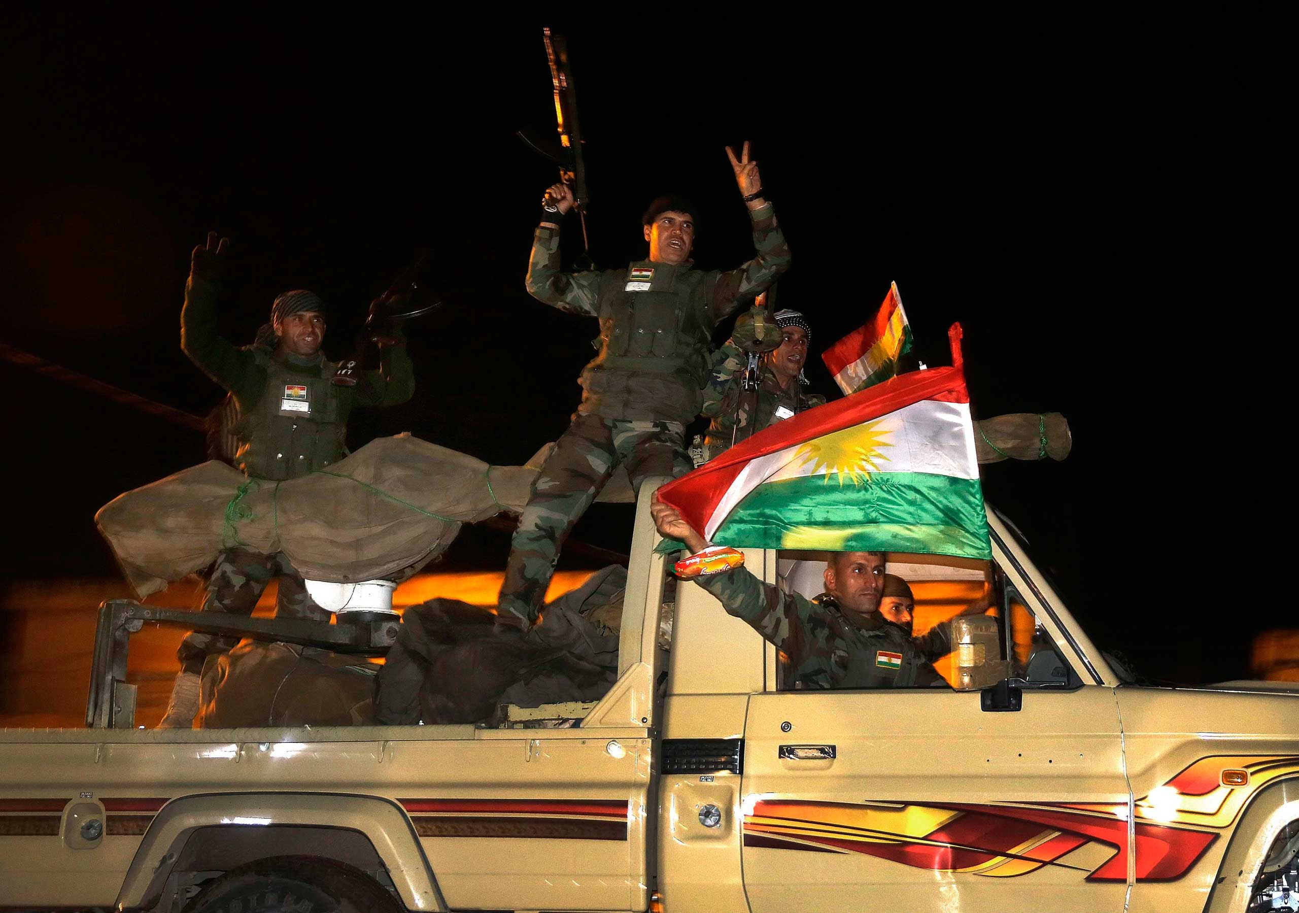 Kurdish peshmerga fighters wave Kurdish flags atop an army vehicle as they move towards the Syrian town of Kobani  from the border town of Suruc, Sanliurfa province, Oct. 31, 2014.