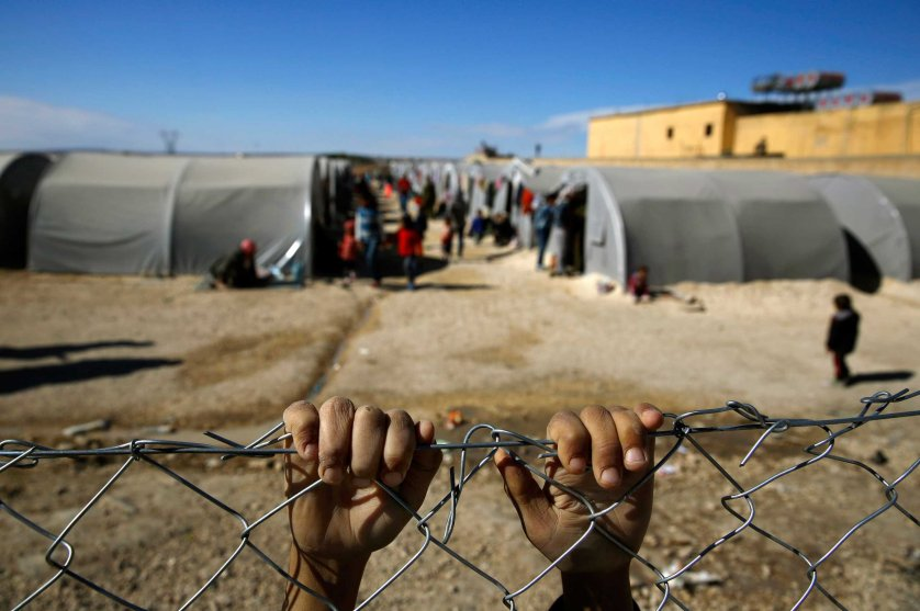Kurdish refugee boy from the Syrian town of Kobani holds onto a fence that surrounds a refugee camp in the border town of Suruc, Sanliurfa province