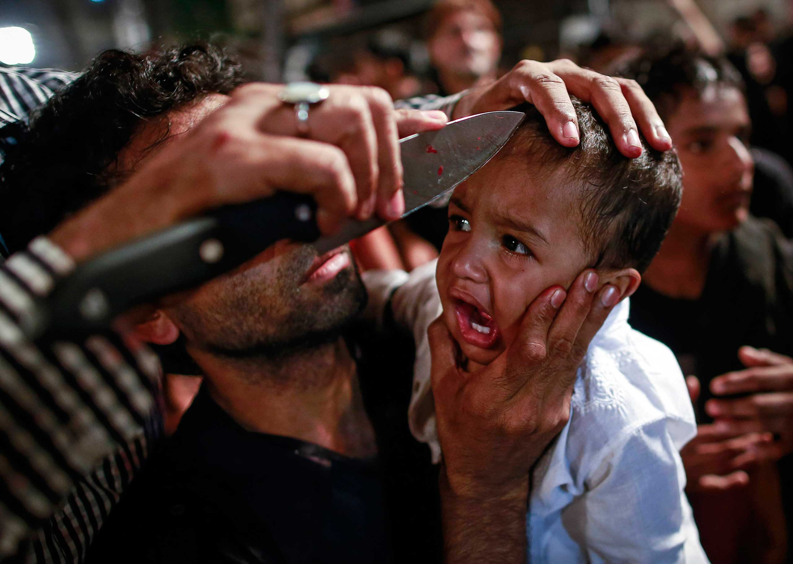 Nov. 3, 2014. A Shiite Muslim has his child gashed with a knife during a Muharram procession ahead of Ashoura in Mumbai.