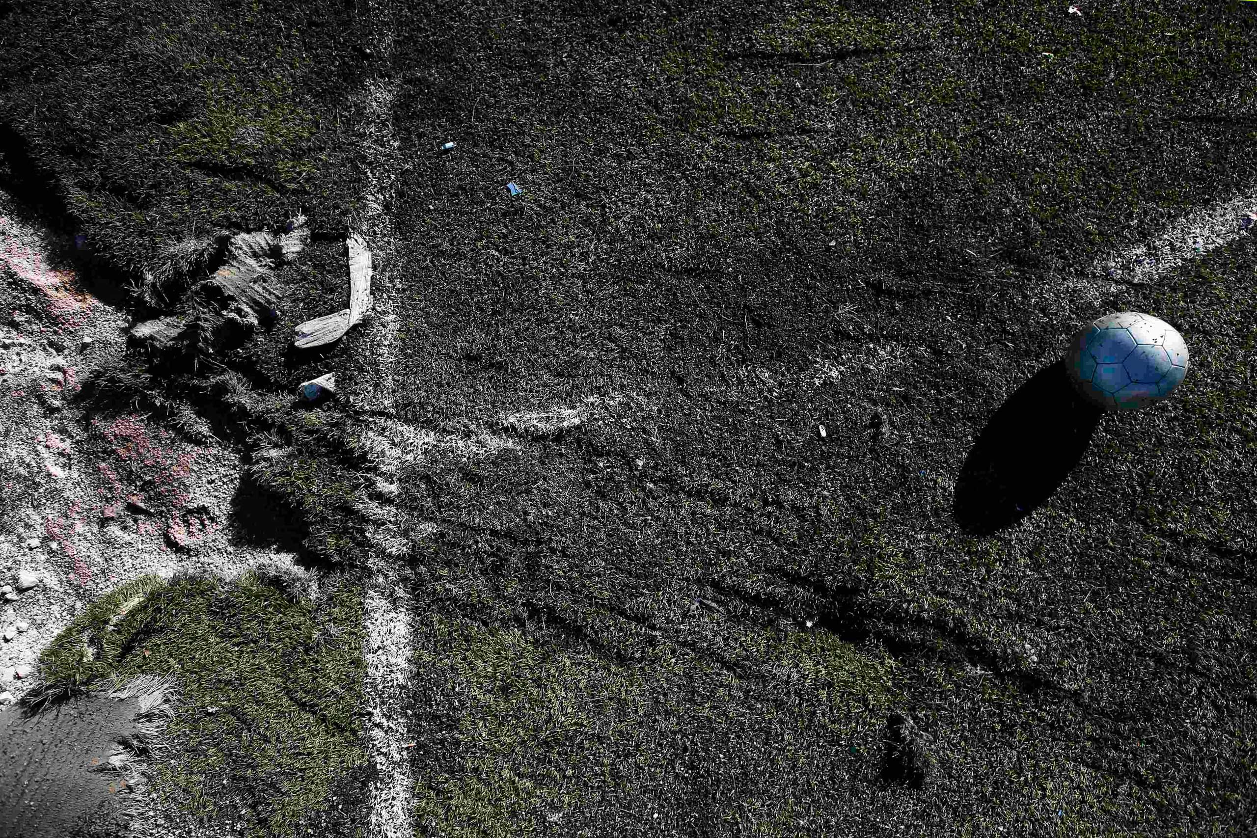Nov. 6, 2014. A ball is seen near a crater caused by shelling at a school's soccer field in Donetsk, eastern Ukraine. Two teenagers died and four were wounded when an artillery shell hit the school's playing field as they played soccer.