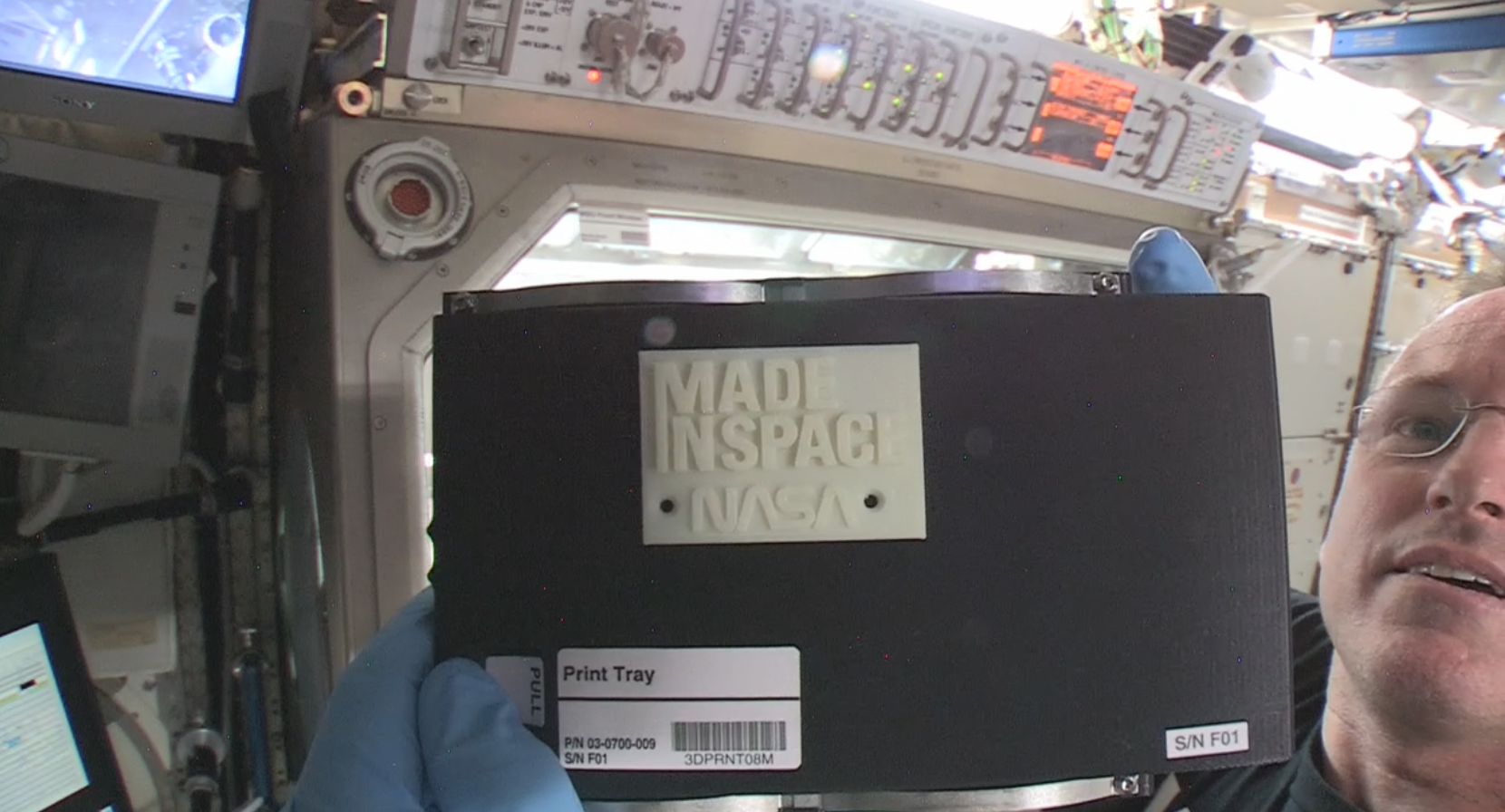 "International Space Station Commander Barry ""Butch"" Wilmore holds up the first object made in space with 3-D printing. Wilmore installed the printer on Nov. 17, 2014, and helped crews on the ground with the first print on Nov. 25, 2014."