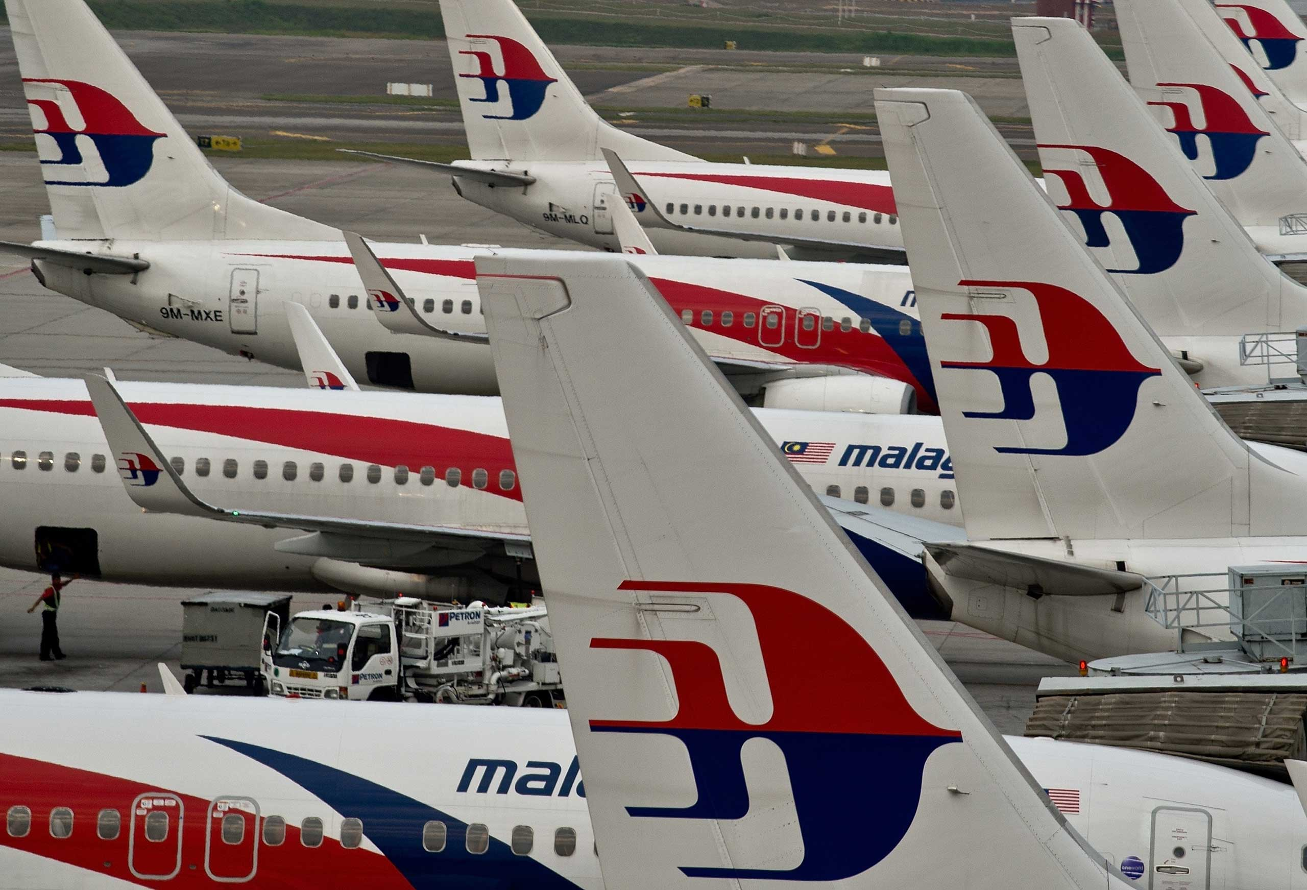 Airport groundstaff walk past Malaysia Airlines planes parked on the tarmac at the Kuala Lumpur International Airport in Sepang on June 17, 2014.
