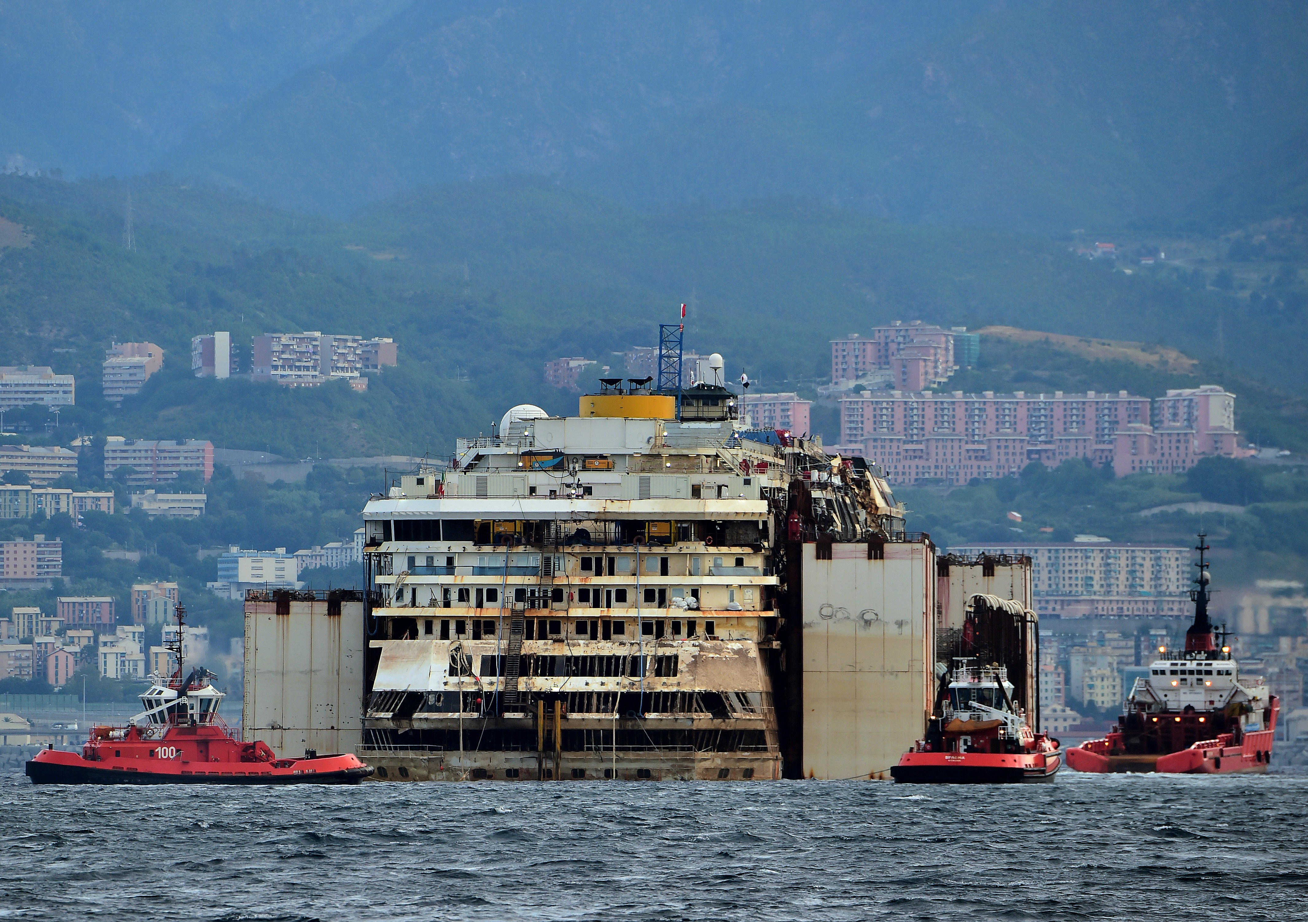 The refloated wreck of the Costa Concordia cruise ship is being dragged to the harbor of Pra di Voltri near Genoa early on July 27, 2014.