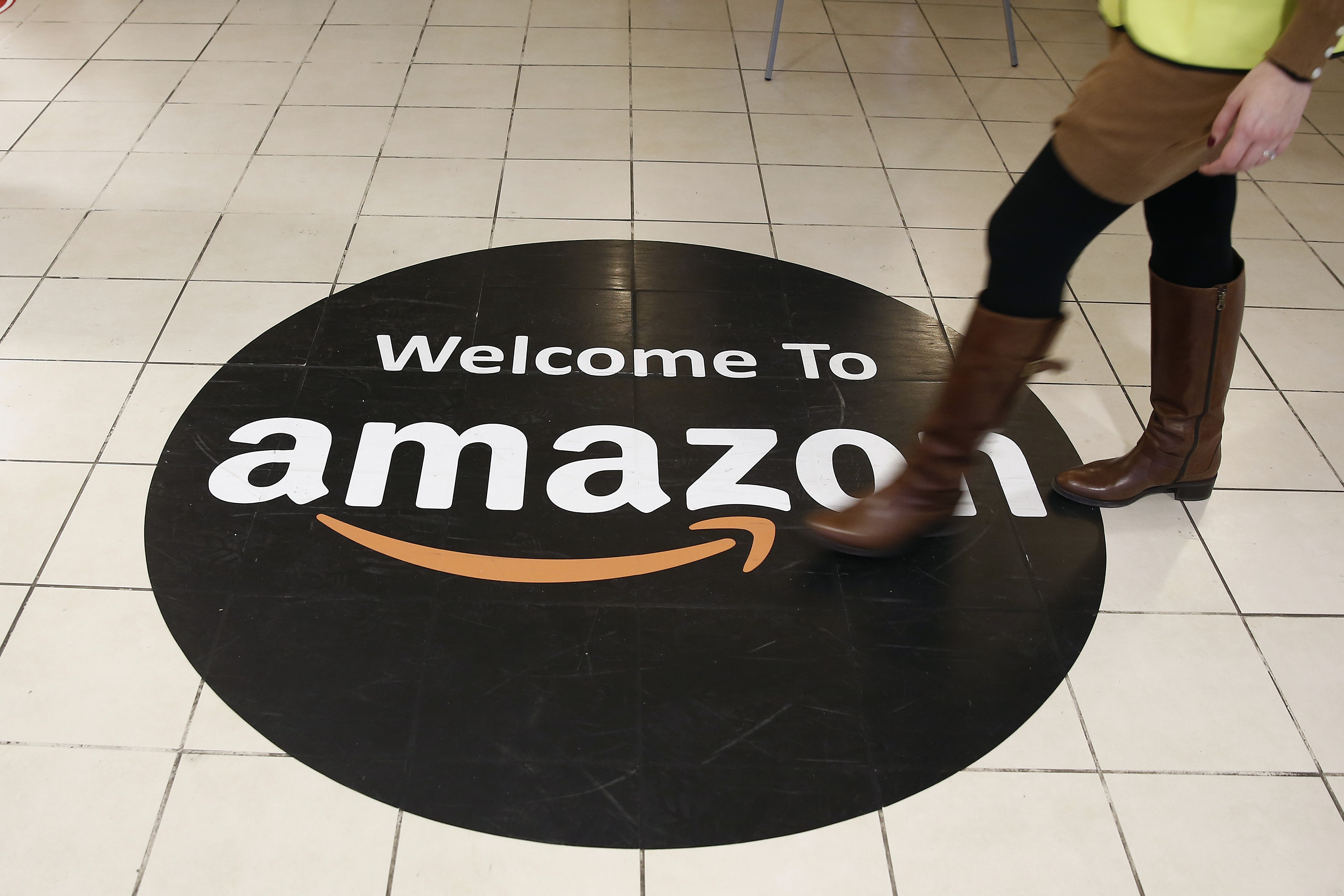 An employee walks over a logo on the floor of Amazon.com Inc.'s fulfillment centers in Rugeley, U.K. on Dec. 2, 2013.