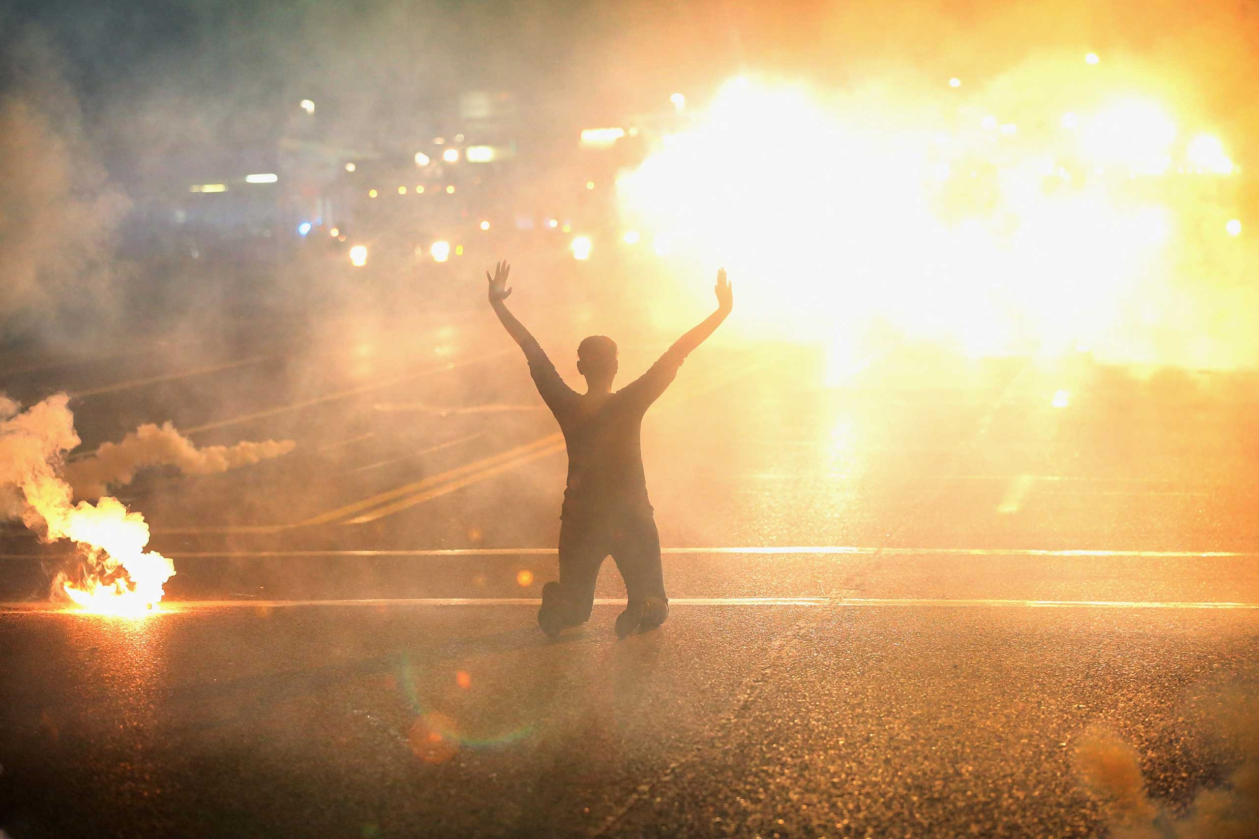Tear gas reigns down on a woman kneeling in the street with her hands in the air after a demonstration over the killing of teenager Michael Brown by a Ferguson police officer on Aug. 17, 2014 in Ferguson, Missouri.