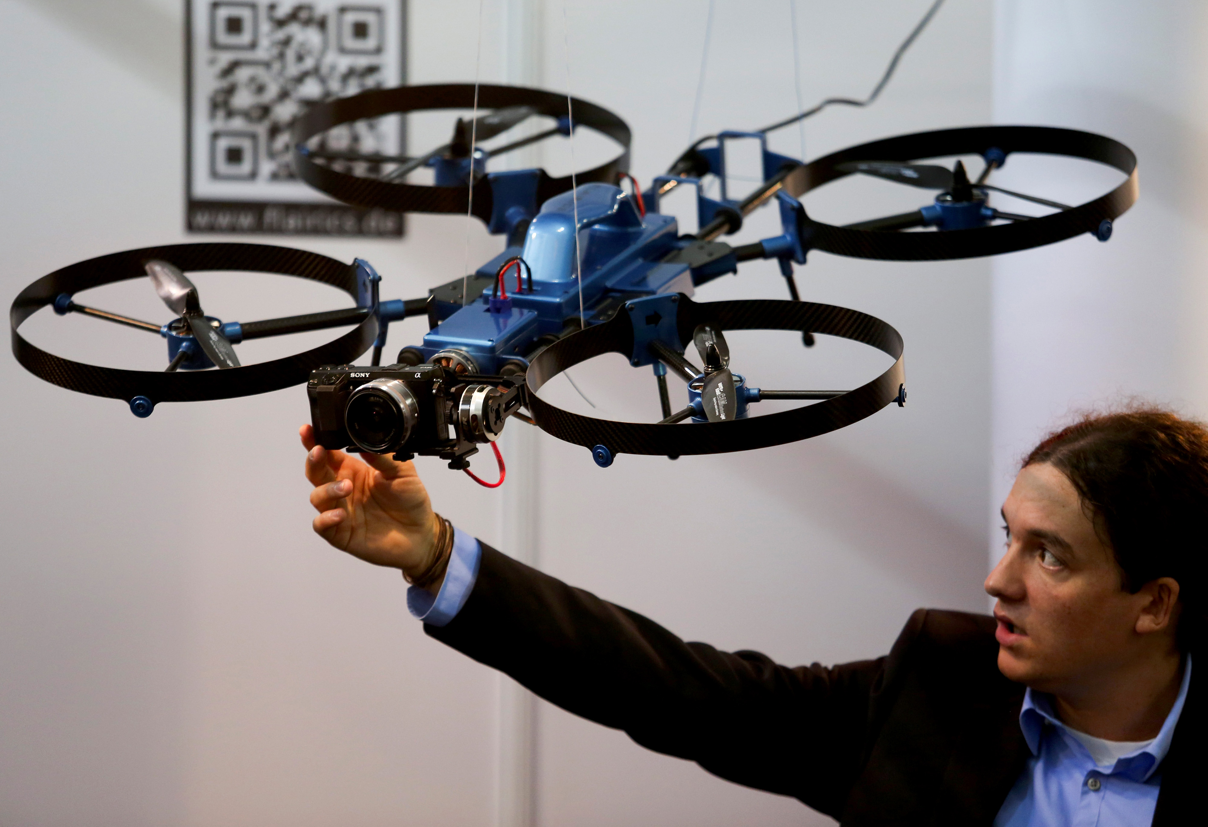 An exhibitor adjusts a Sony Corp. digital camera mounted to a drone, developed by Flairics GmbH and Co., as it hangs on display during the Commercial UAV show in London, U.K., on Tuesday, Oct. 21, 2014.