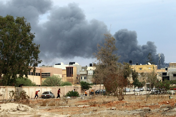 A picture taken on October 22, 2014 in the Libya's eastern coastal city of Benghazi shows smoke billowing from buildings after the Libyan airforce, loyal to former general Khalifa Haftar, pounded the buildings were reported to be used for storing ammunition belonging to Benghazi-based Islamist Ansar al-Sharia group. Fierce fighting have been raging for days in several parts of Libya's second city between pro-government forces led by Haftar and Islamist militias. AFP PHOTO / ABDULLAH DOMA        (Photo credit should read ABDULLAH DOMA/AFP/Getty Images)
