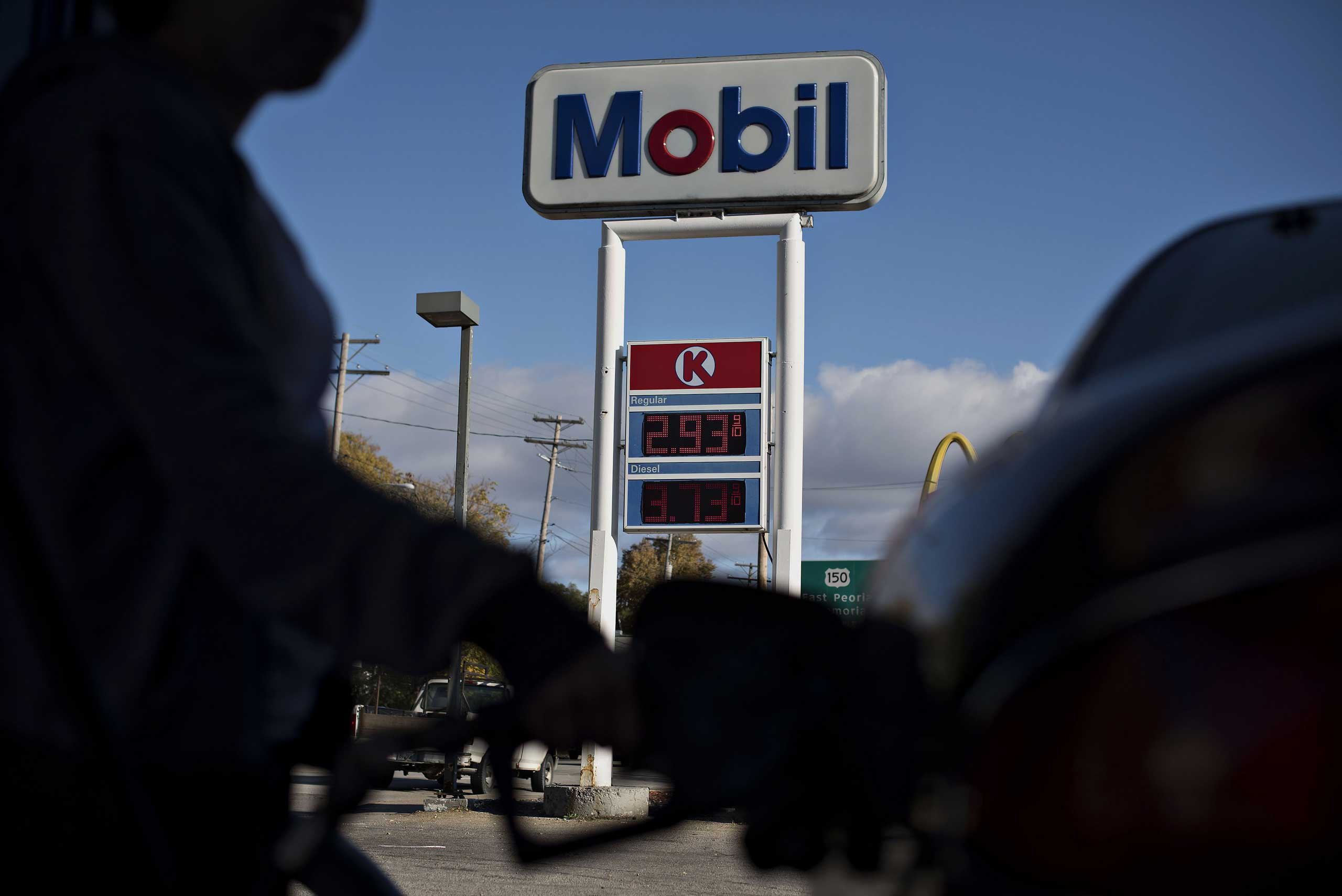 Gas prices are displayed as a customer fuels a vehicle at a Mobil gas station in Peoria, Illinois, U.S., on Oct. 29, 2014.