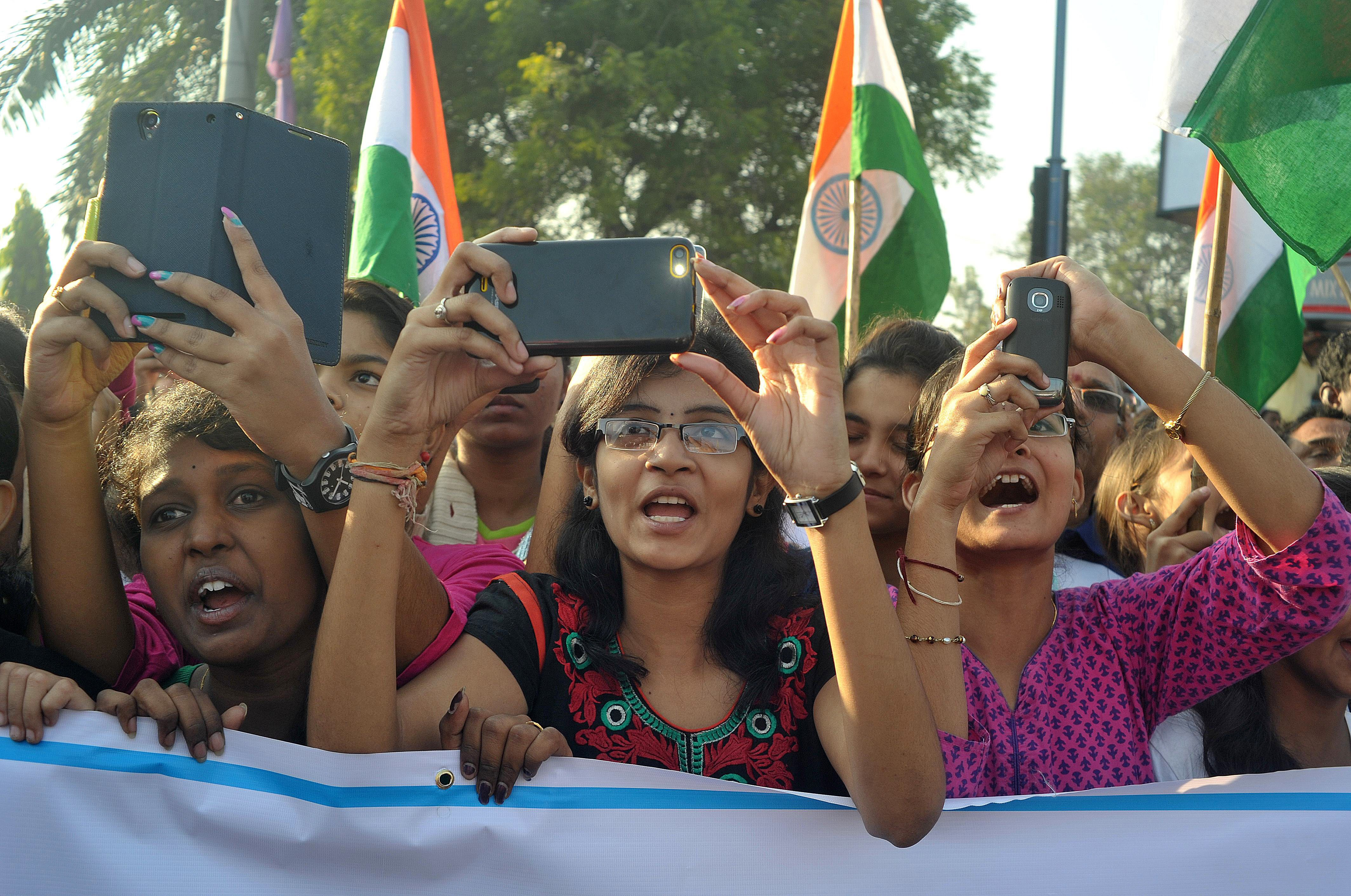 Indian students use cellphones to photograph unseen Central Home Minister of India Rajnath Singh during a Run for Unity event to mark the anniversary of the birth of Sardar Vallabhbhai Patel in Hyderabad on October 31, 2014.
