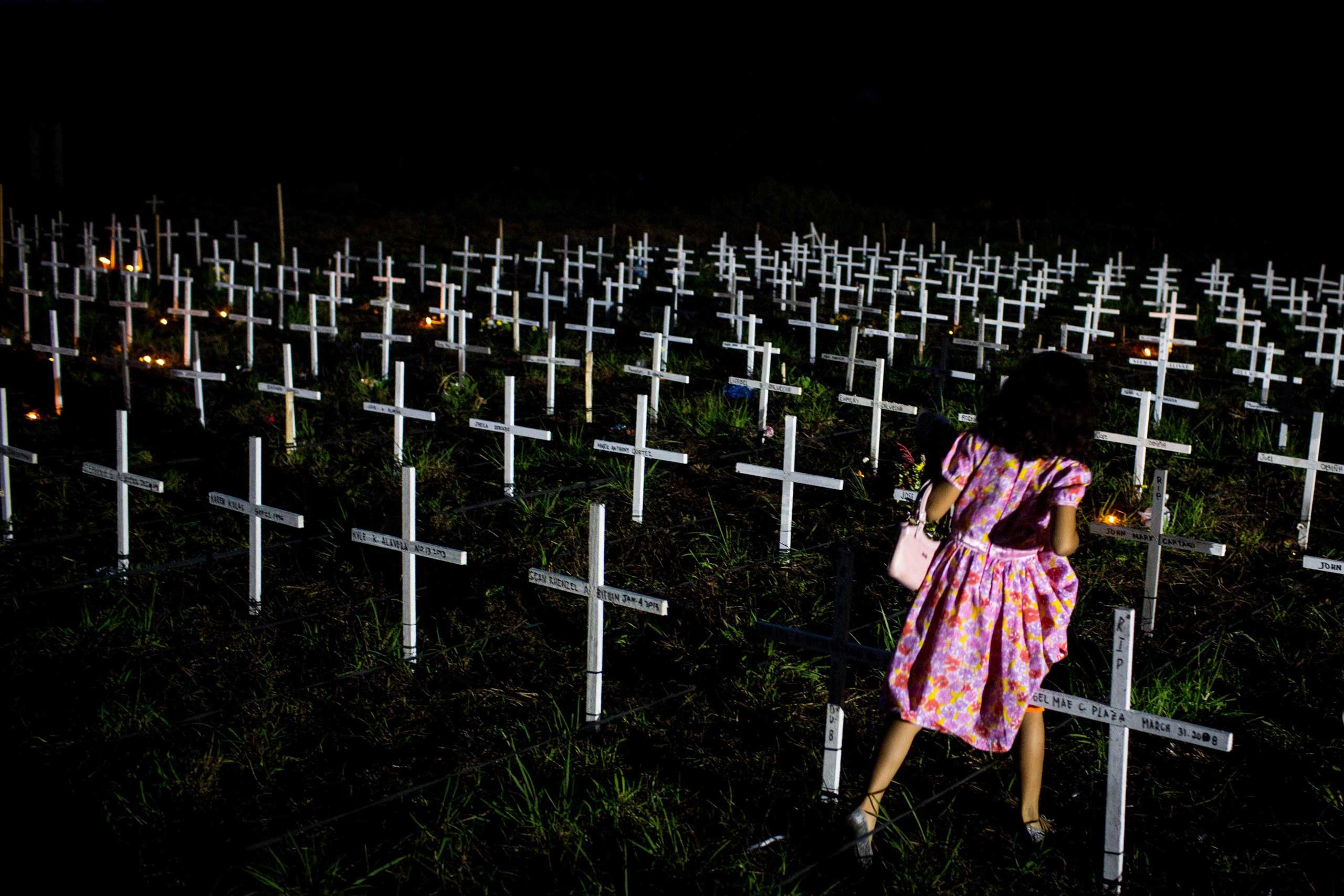 Nov. 2, 2014. A young girl walks between crosses as she tries to find the  grave of a loved one at a newly constructed mass grave for 3,000 typhoon Haiyan victims on the grounds of the Holy Cross Cemetery during All Souls Day in Tacloban, Leyte, Philippines.