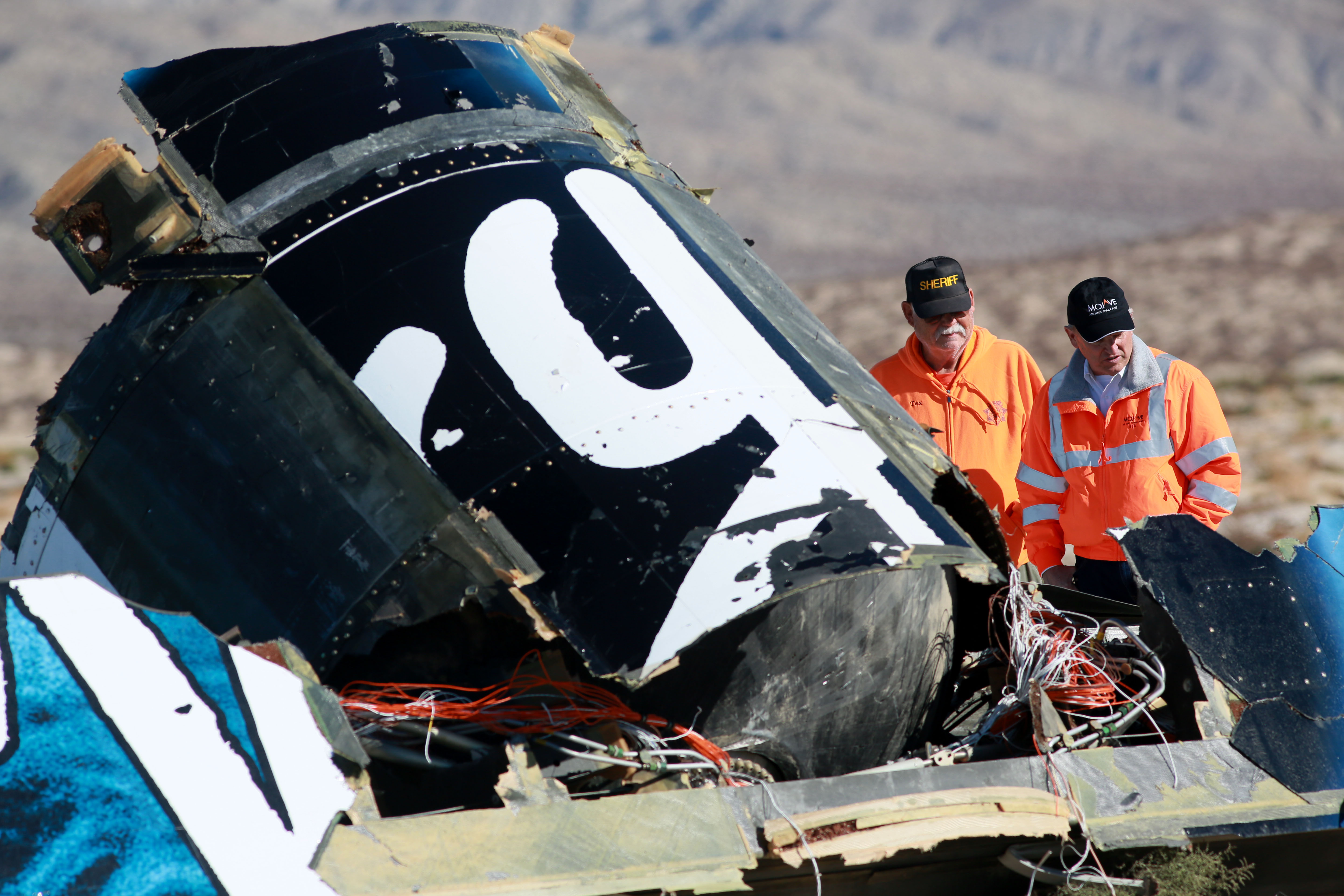 Sheriff's deputies inspect the wreckage of the Virgin Galactic SpaceShip 2 in a desert field November 2, 2014 north of Mojave, California on The Virgin Galactic SpaceShip 2 crashed on October 31, 2014 during a test flight, killing one pilot and seriously injuring another.