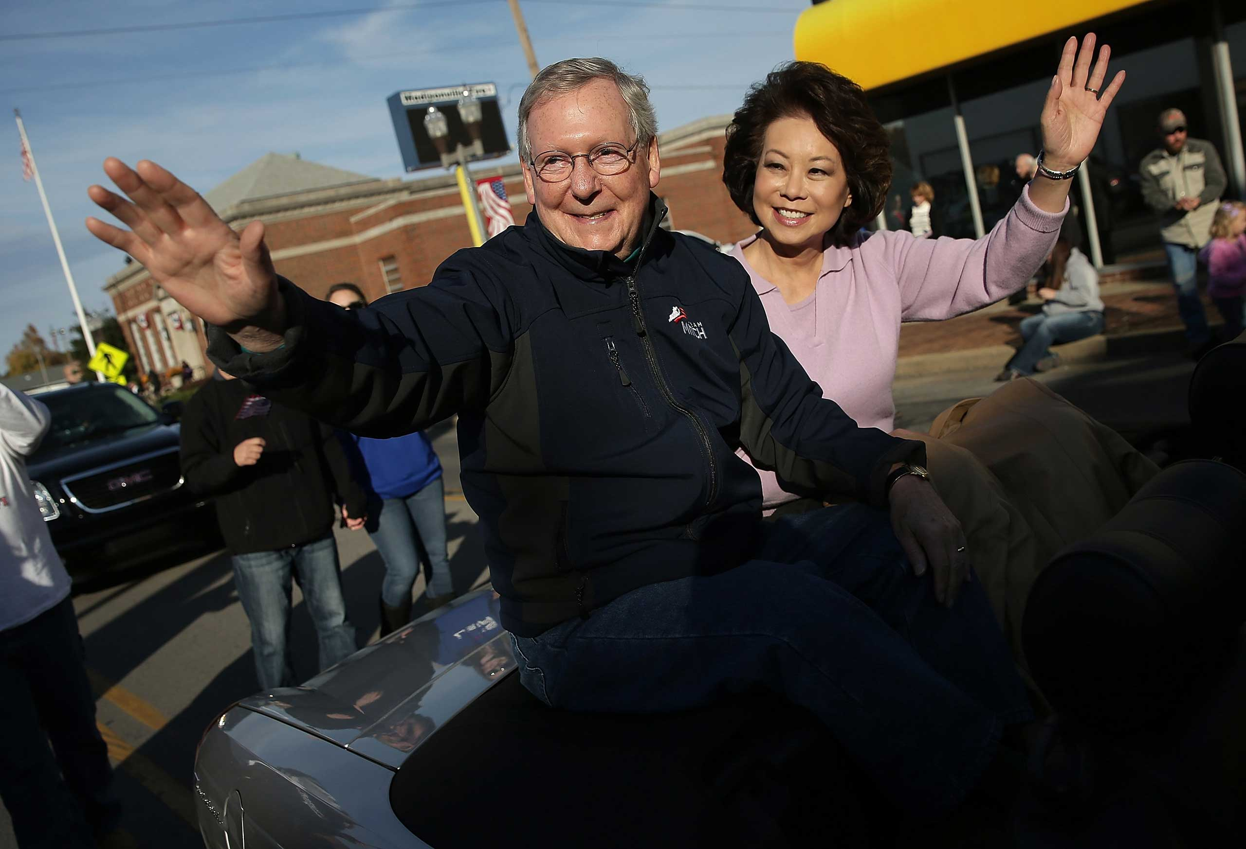 Senate Minority Leader Mitch McConnell (R-KY) waves while riding with his wife Elaine Chao (R) in the Hopkins Country Veterans Day Parade on November 2, 2014 in Madisonville, Ky.
