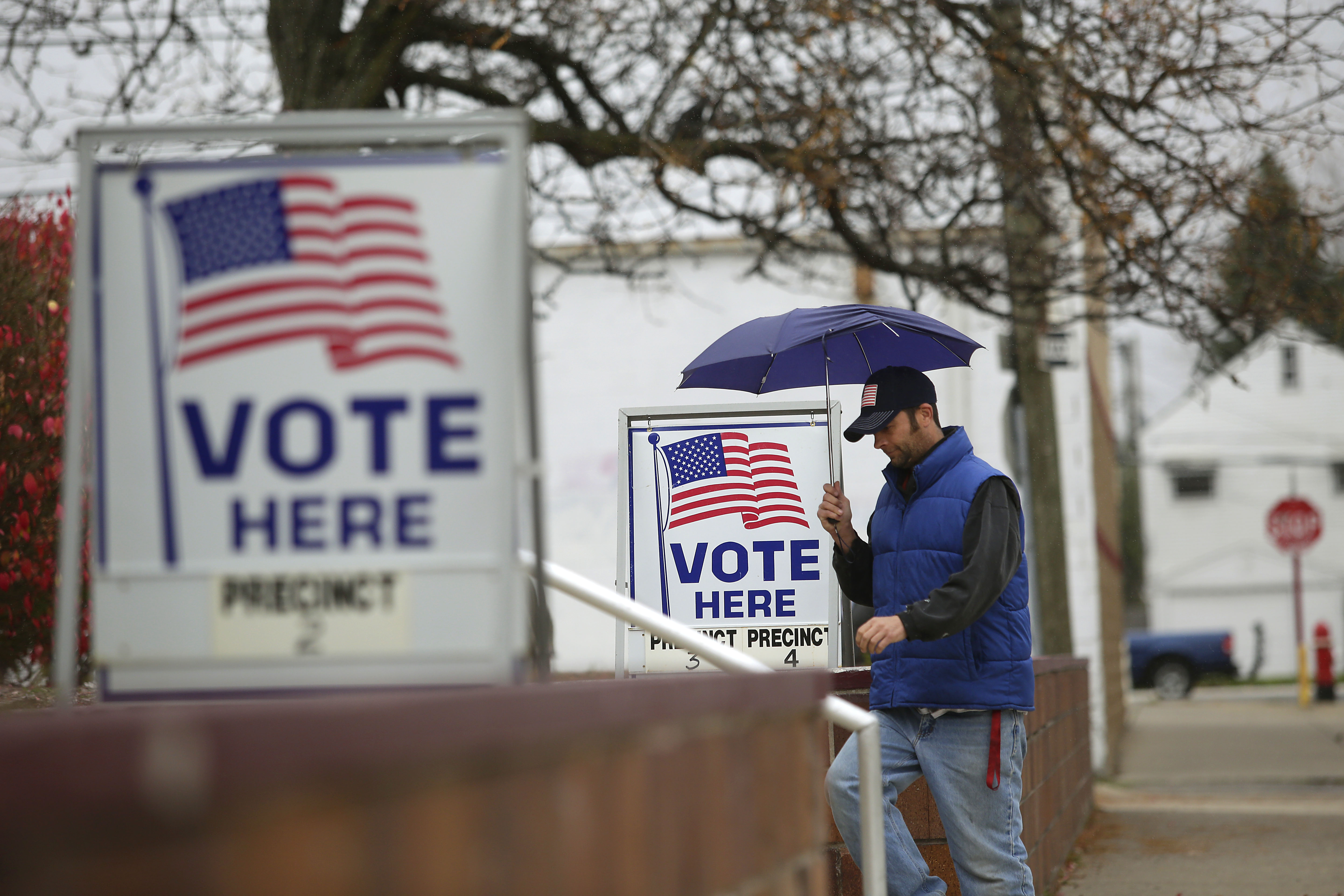 A man fills walks past voting signs displayed outside a polling station during the mid-term elections November 4, 2014 in Hamtramck, Michigan.