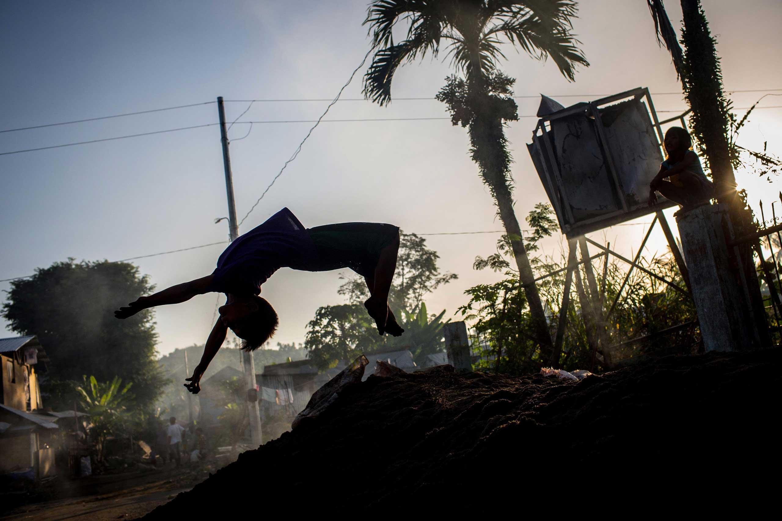 Nov. 6, 2014. A boy does a backflip off a mound of dirt in San Antonio, Samar, Philippines.