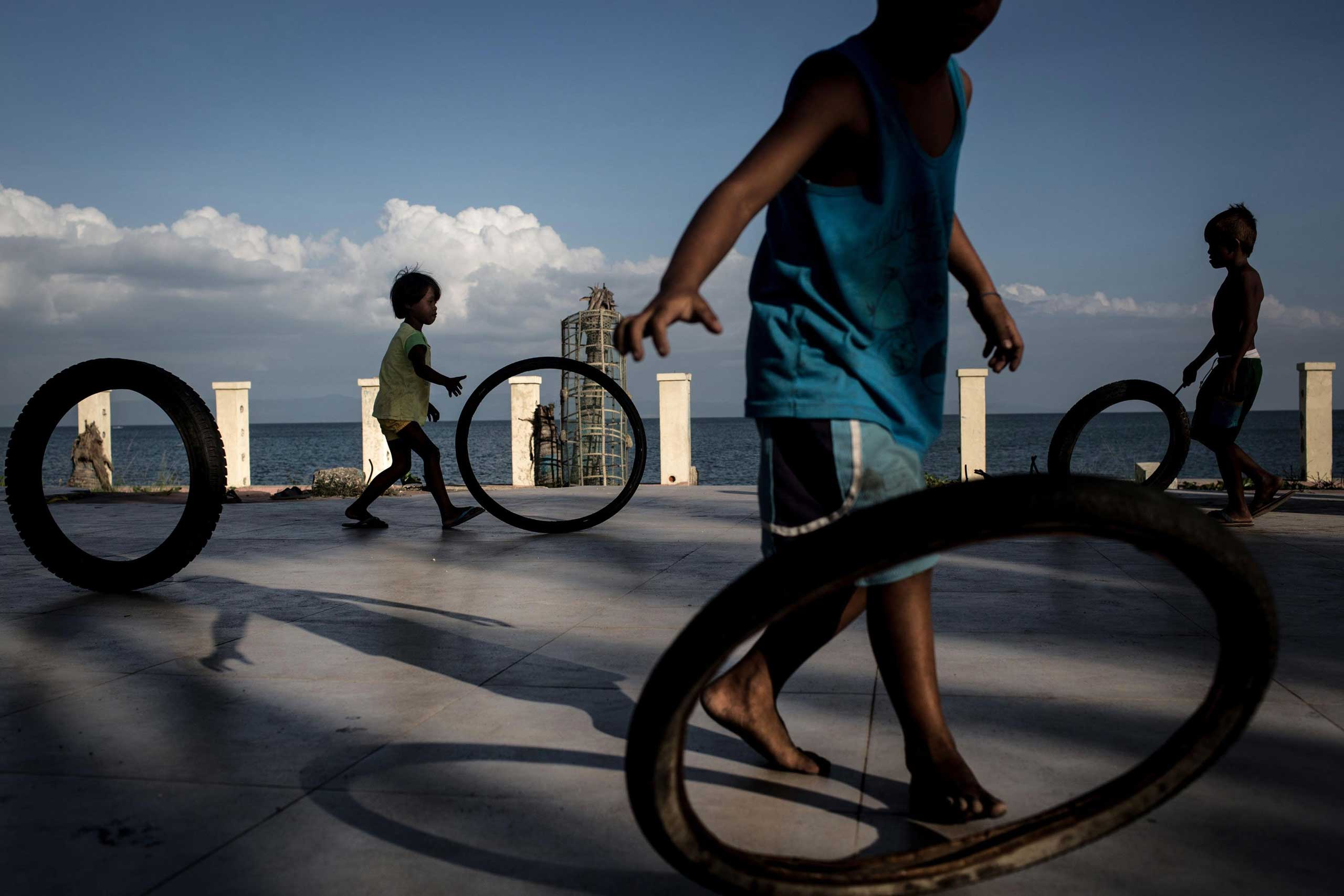 Nov. 6, 2014. Children play with bike tires in a destroyed resort building on the coastline at San Jose in Tacloban, Leyte, Philippines. Residents of Leyte are preparing for the 1-year anniversary since Super Typhoon Yolanda struck the coast on November 8, 2013, leaving more than 6000 dead and many more homeless.