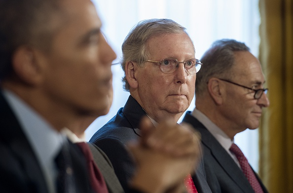 Mitch McConnell, R-Kentucky, center, looks on as U.S. President Barack Obama, left, speaks during a bipartisan, bicameral congressional leadership luncheon at the White House in Washington, D.C., Nov. 7, 2014