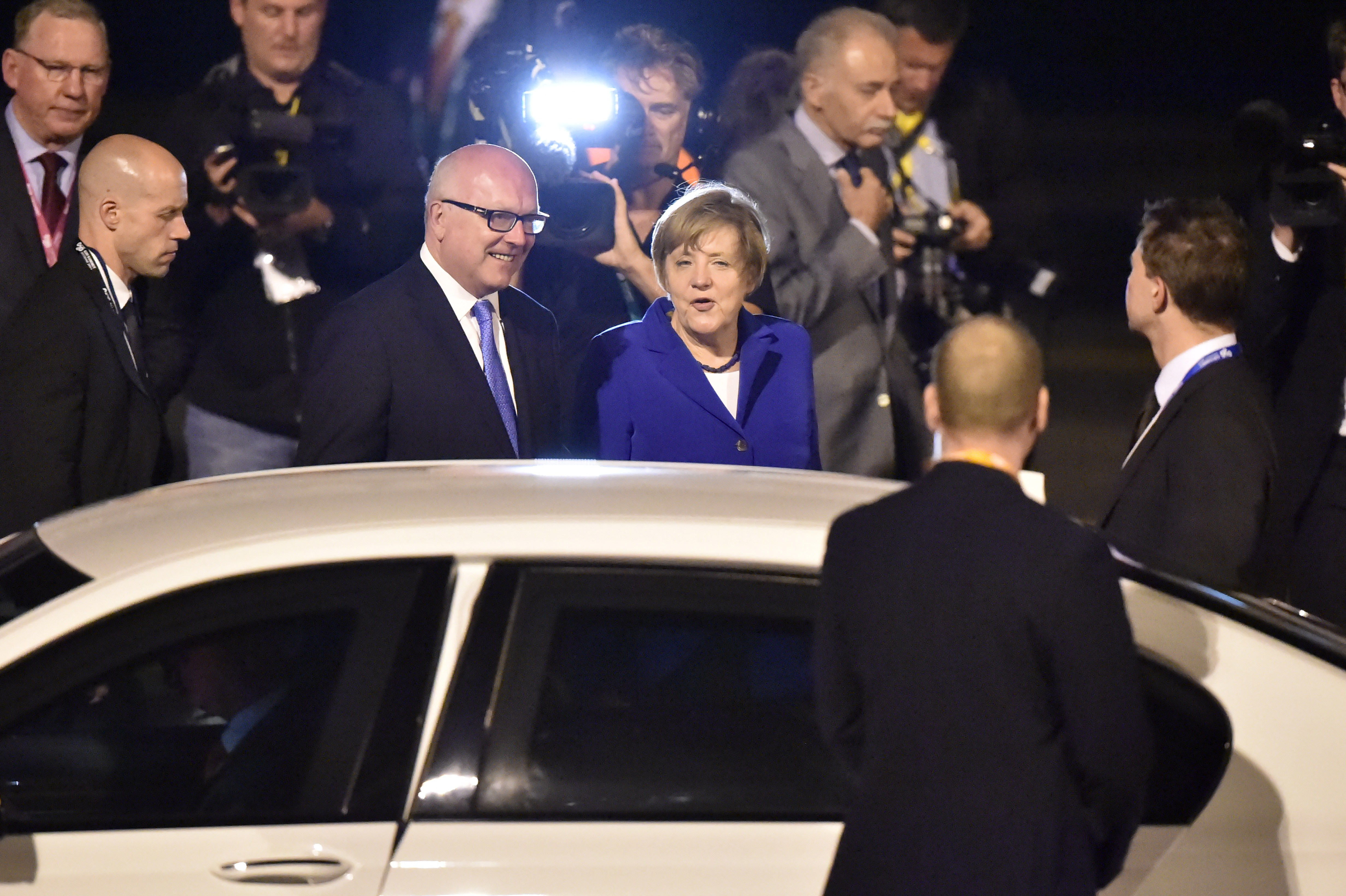 Germany's Chancellor Angela Merkel (C) is welcomed upon her arrival at the airport in Brisbane to take part in the G20 summit on November 14, 2014.