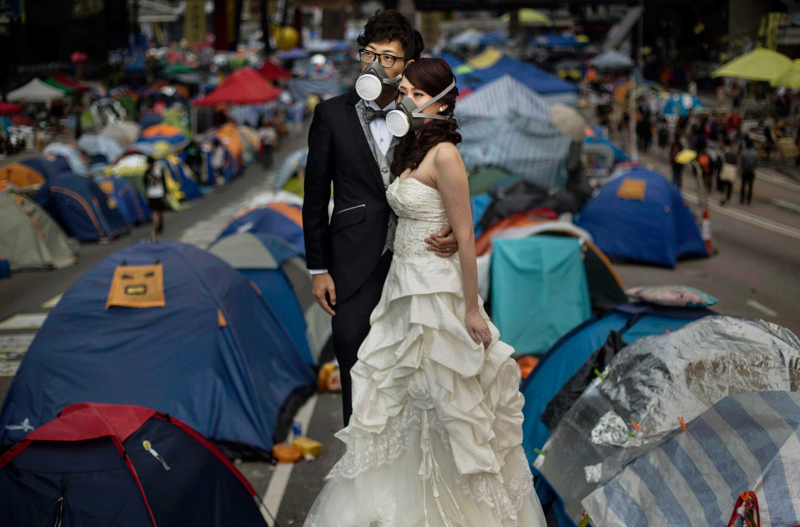 Nov. 14, 2014. A young Hong Kong couple wear gas masks as they pose for a wedding photographer prior to their marriage next to the tents used by pro-democracy demonstrators at the Admiralty protest site on  in Hong Kong,
