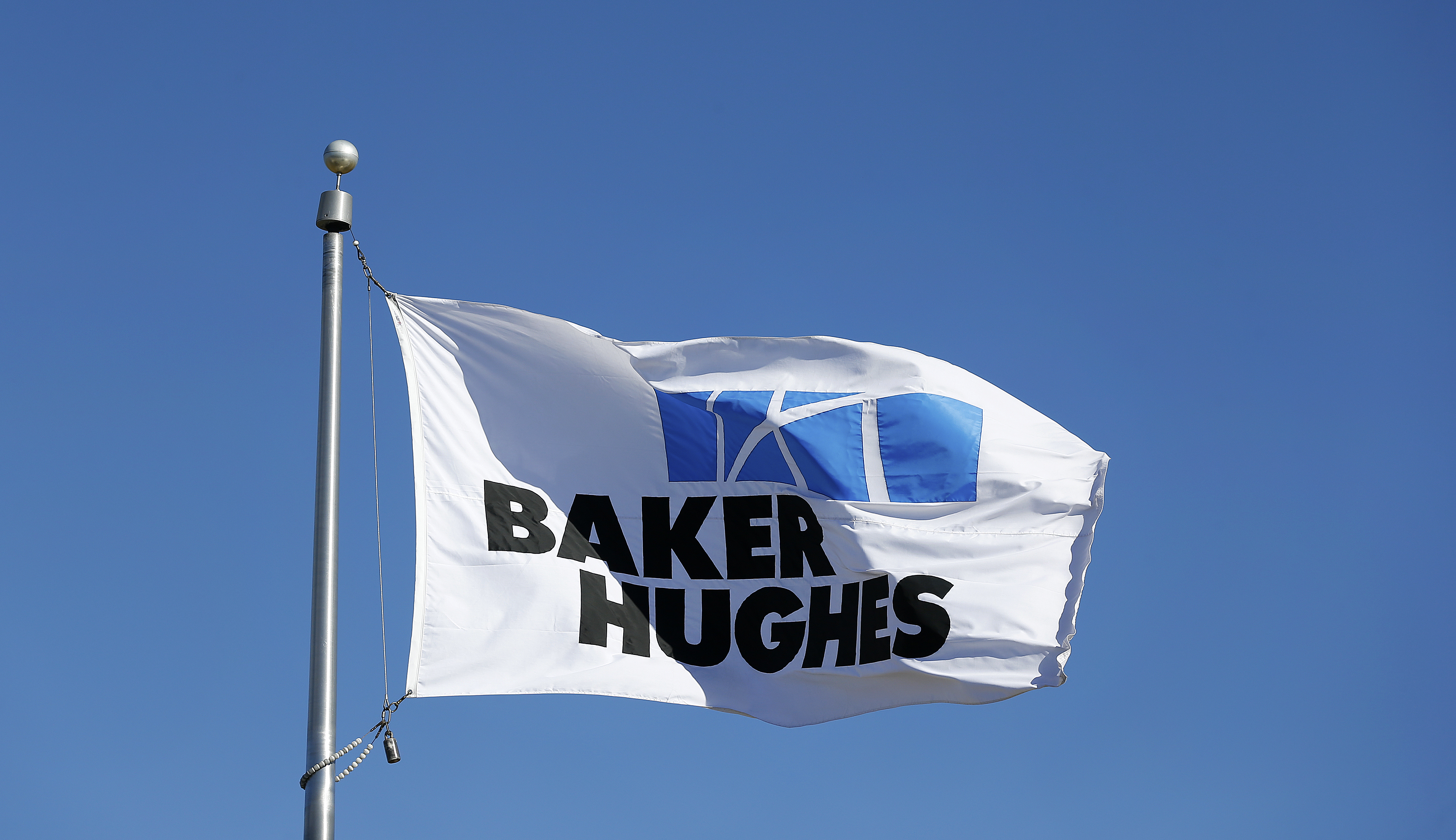 A flag with the Baker Hughes Inc. logo flies outside one of the company's facilities in Houston, Texas, U.S., on Monday, Nov. 17, 2014.