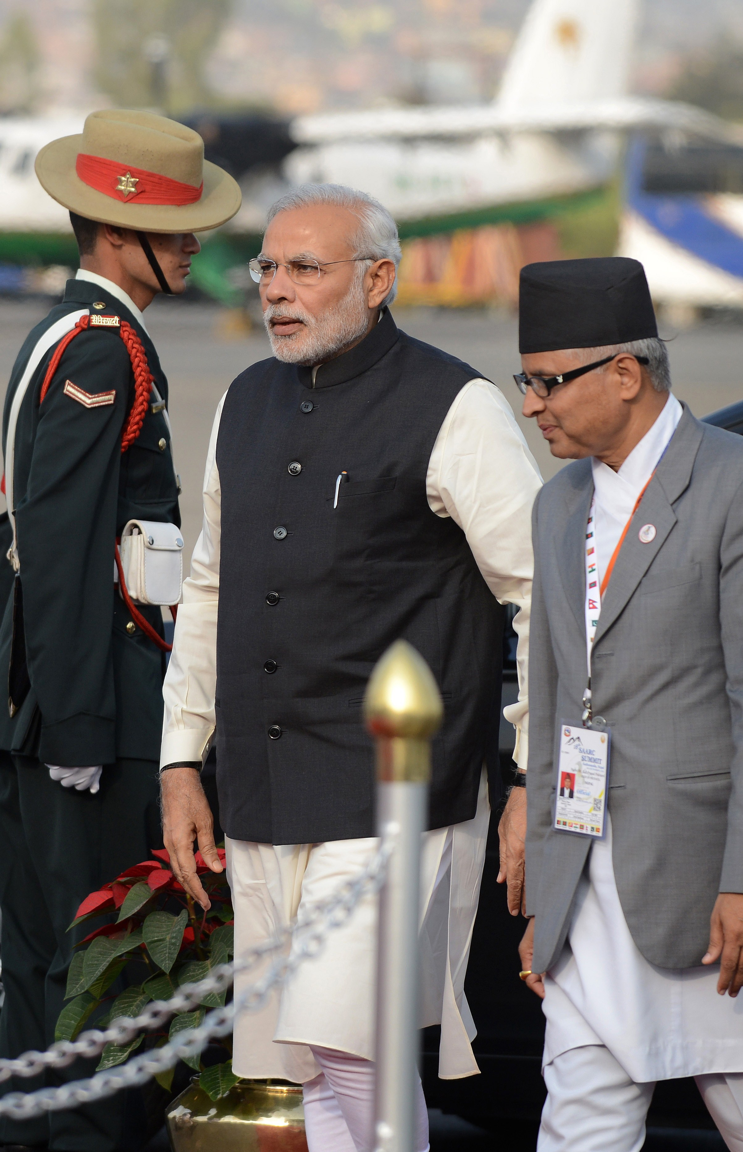 Indian Prime Minister Narendra Modi (L) walks on his arrival at Tribhuvan International Airport to attend the 18th South Asian Association for Regional Cooperation (SAARC) summit in Kathmandu on November 25, 2014.