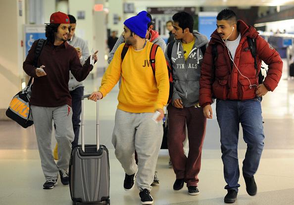 A group of friends traveling to San Francisco, Calif., walk through the terminal at Philadelphia International Airport Nov. 26, 2014 in Philadelphia, Pennsylvania