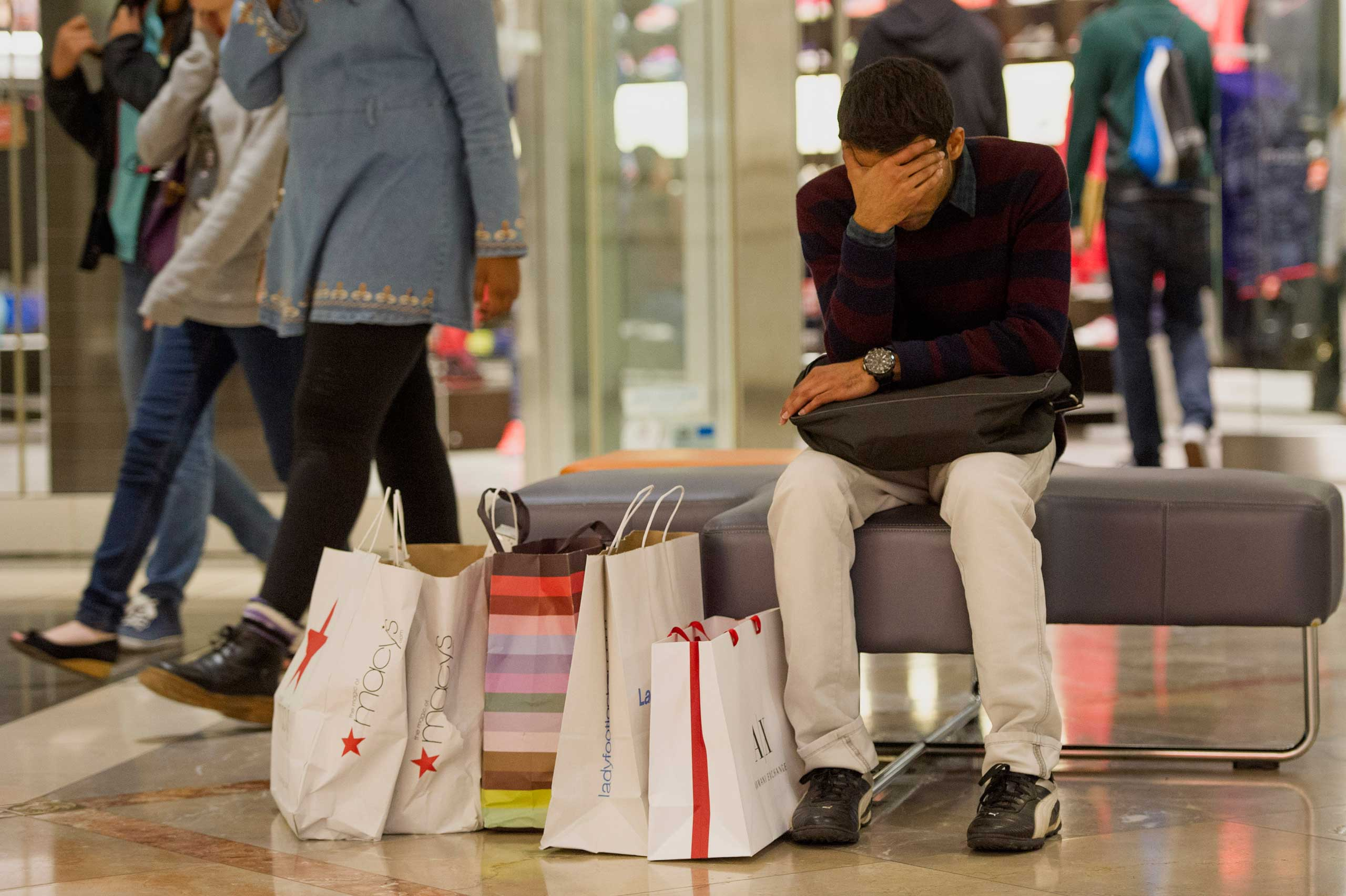 A man takes a break from shopping inside the Westfield San Francisco Centre on Black Friday in San Francisco, Nov. 28, 2014.